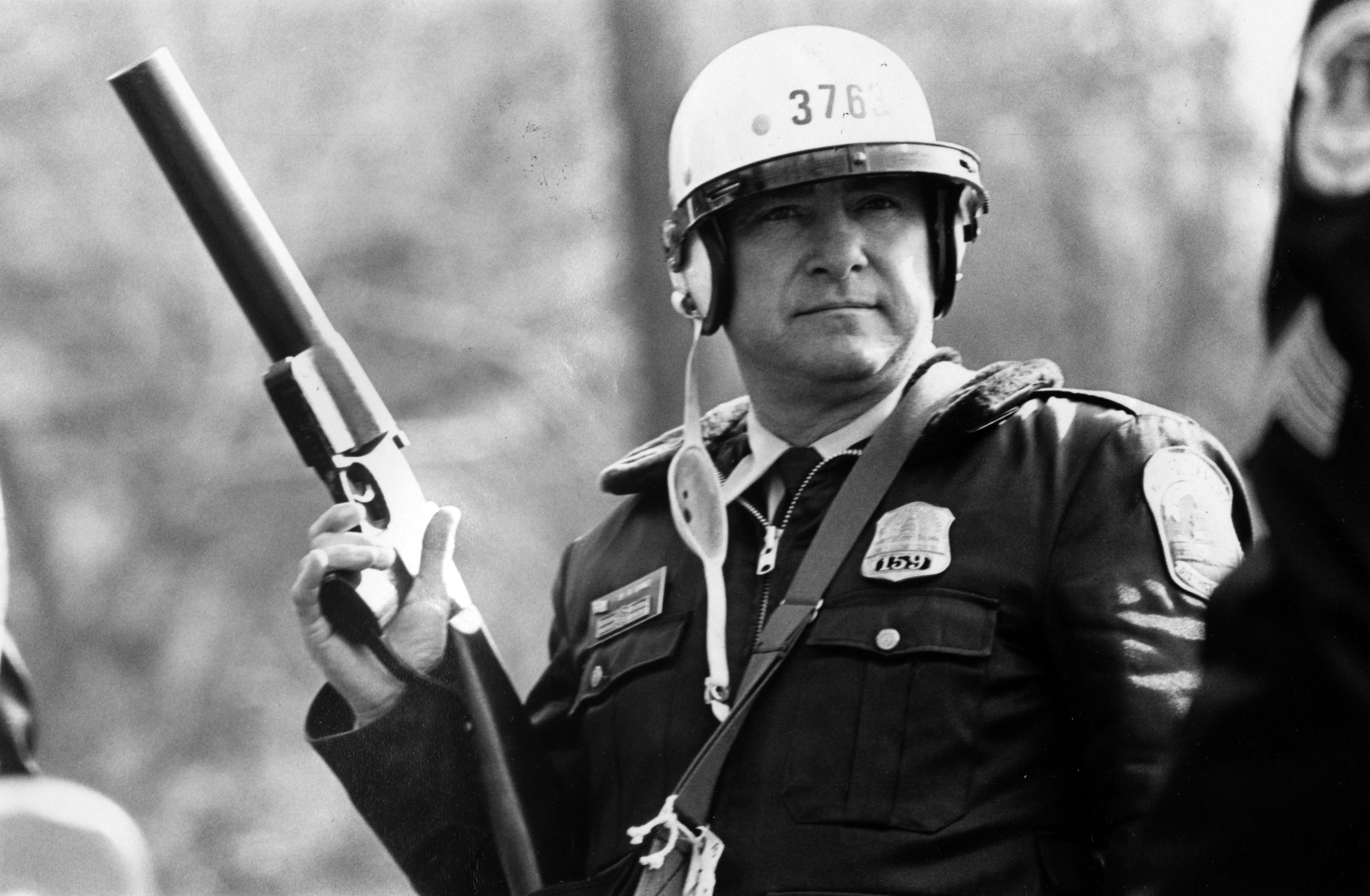 A police officer with a tear gas gun during an anti-Ku Klux Klan protest in Washington D.C., November, 1982.