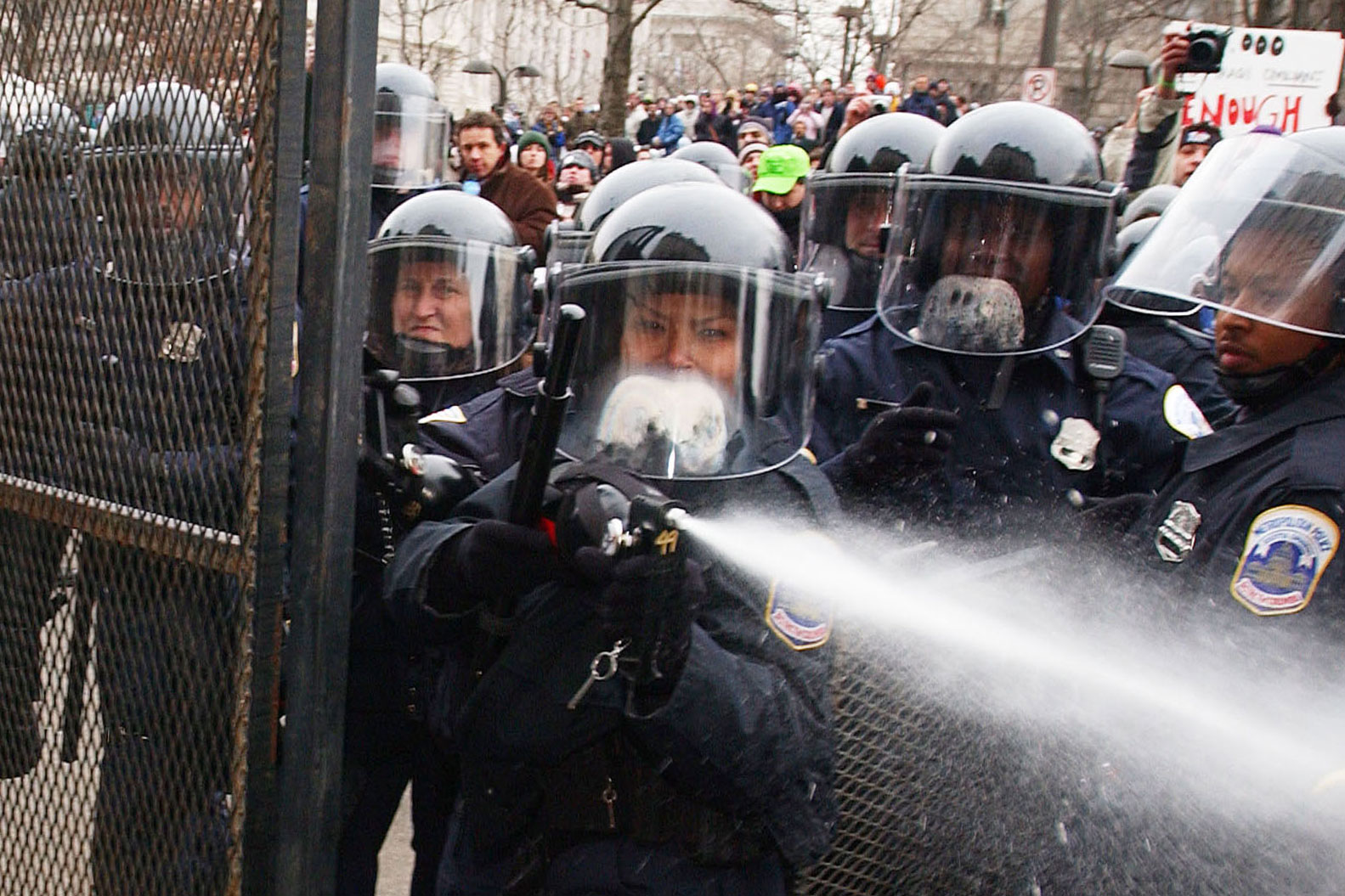 A Washington, D.C., police officer pepper sprays demonstrators after a barricade along Pennsylvania Avenue was pulled down during the inaugural parade, January 20, 2005.