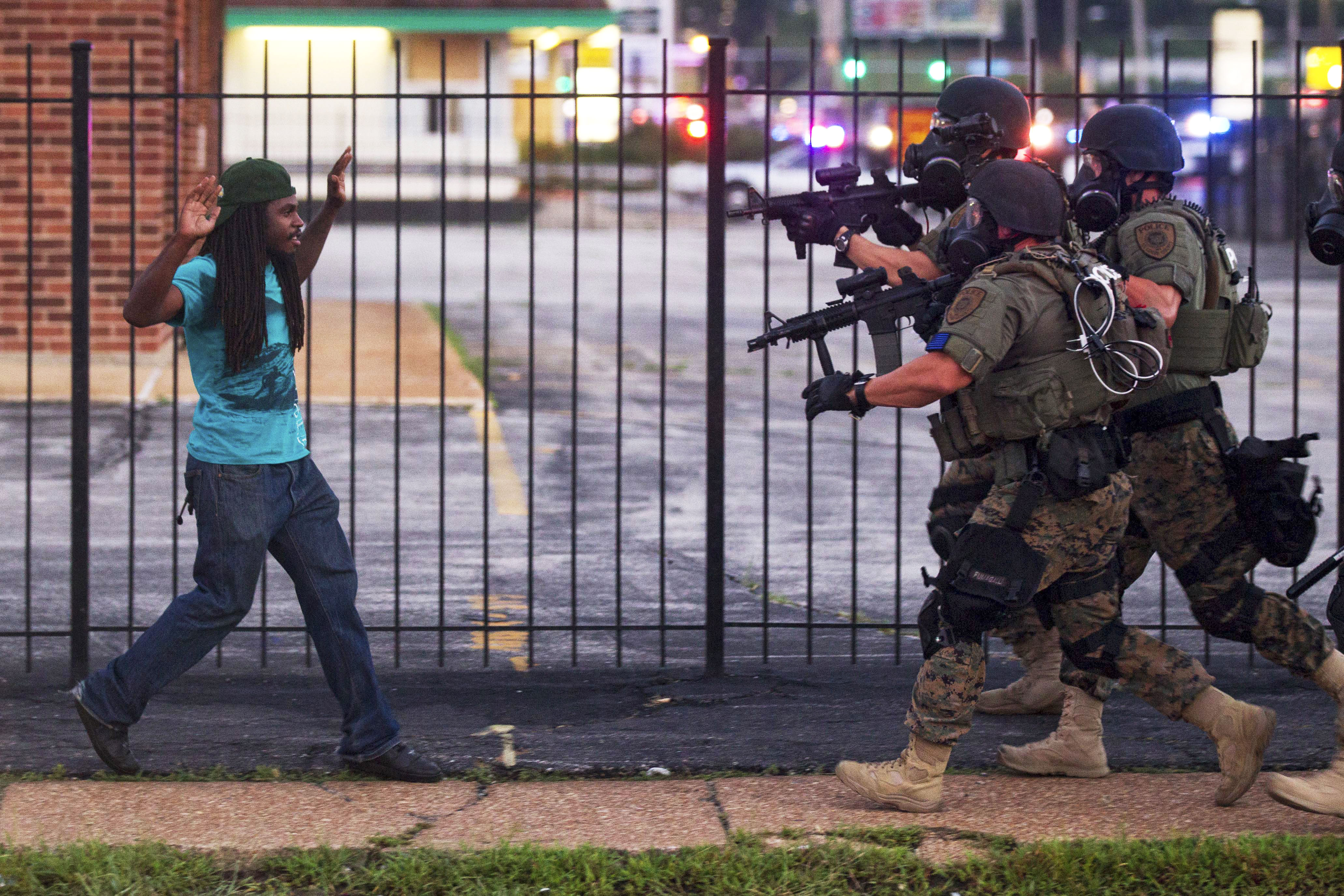 A man backs away as police close in on him during unrest in Ferguson, Mo. following Michael Brown's death, Aug. 11, 2014.
