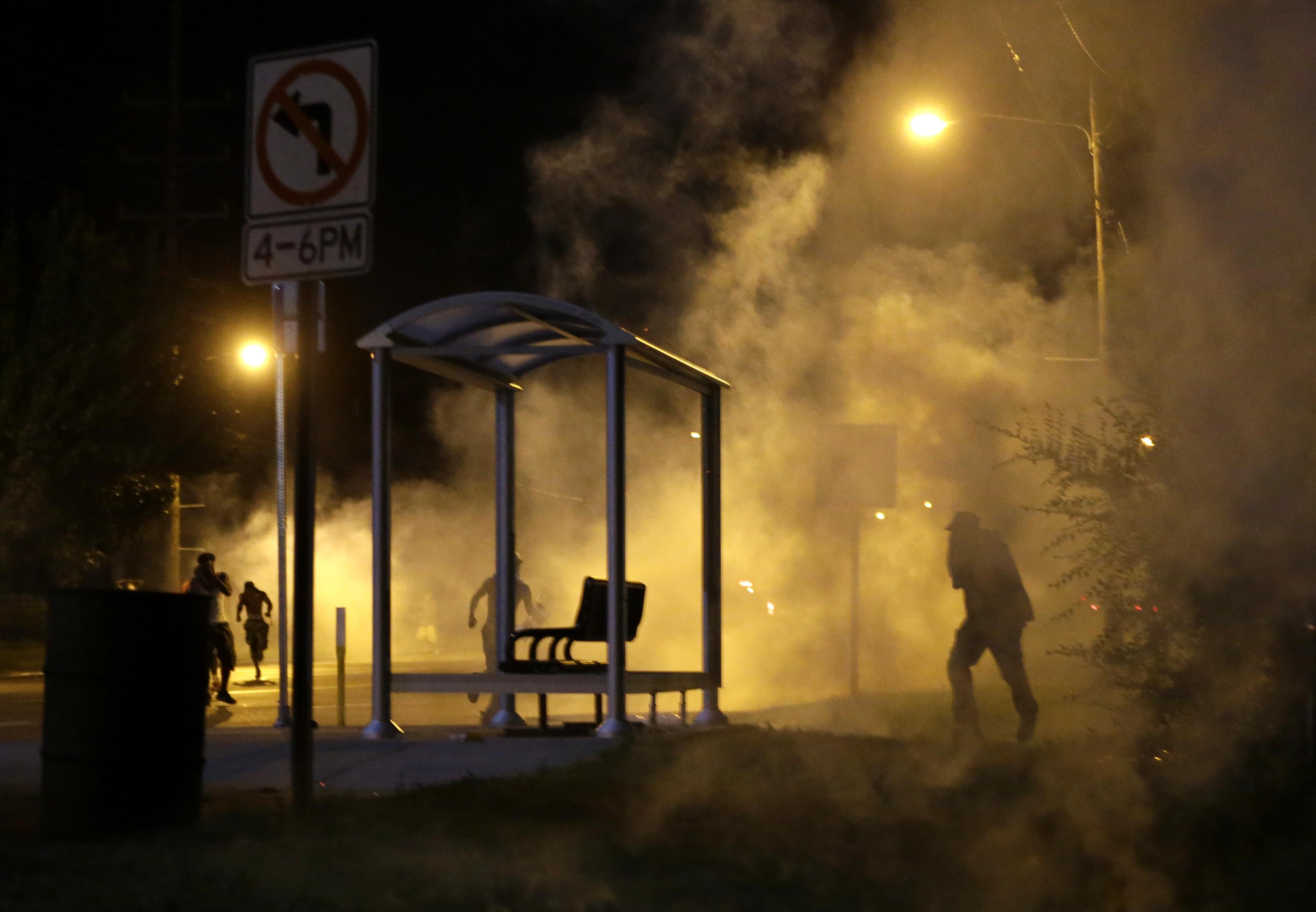 People run through smoke in Ferguson, Mo. on Aug. 13, 2014.