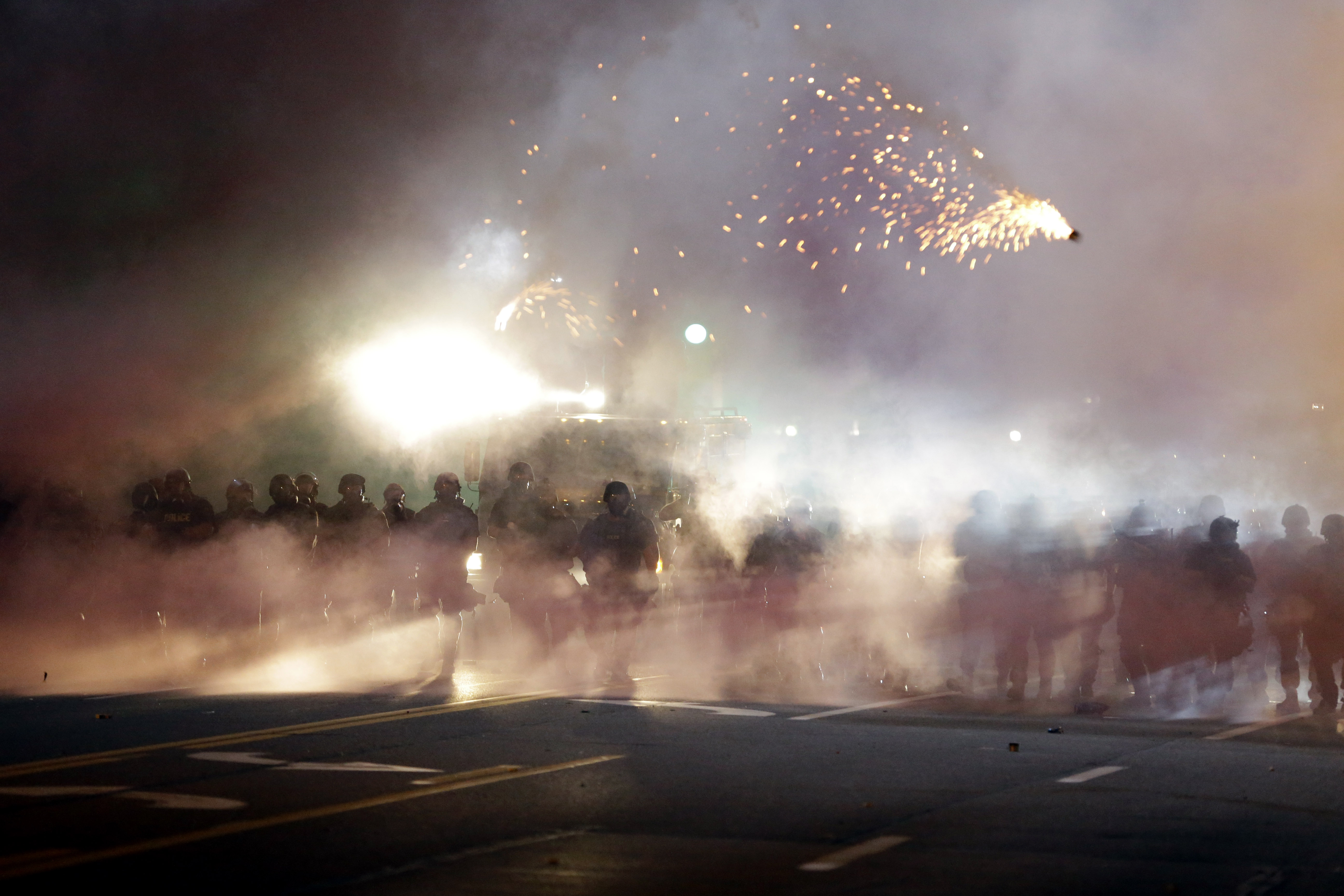An explosive device deployed by police flies in the air as police and protesters clash in Ferguson, Mo., on Aug. 13, 2014