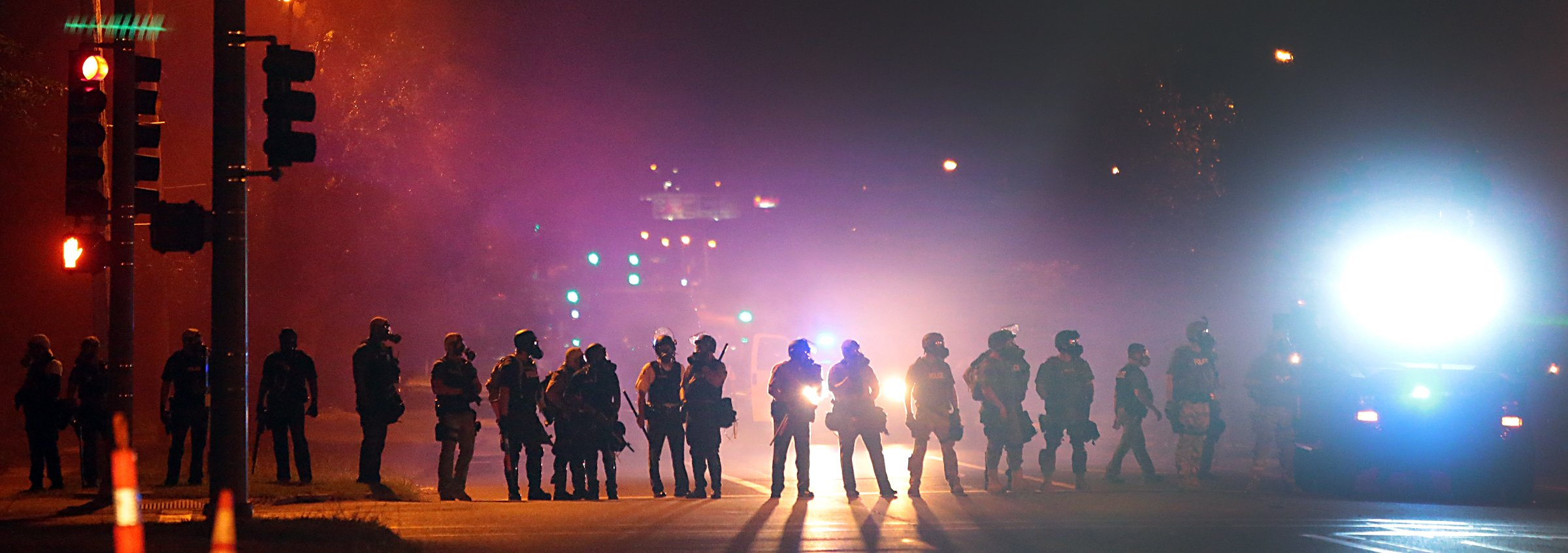 Police officers work their way north on West Florissant Avenue clearing the road of people in Ferguson, Mo. on Aug. 13, 2014.