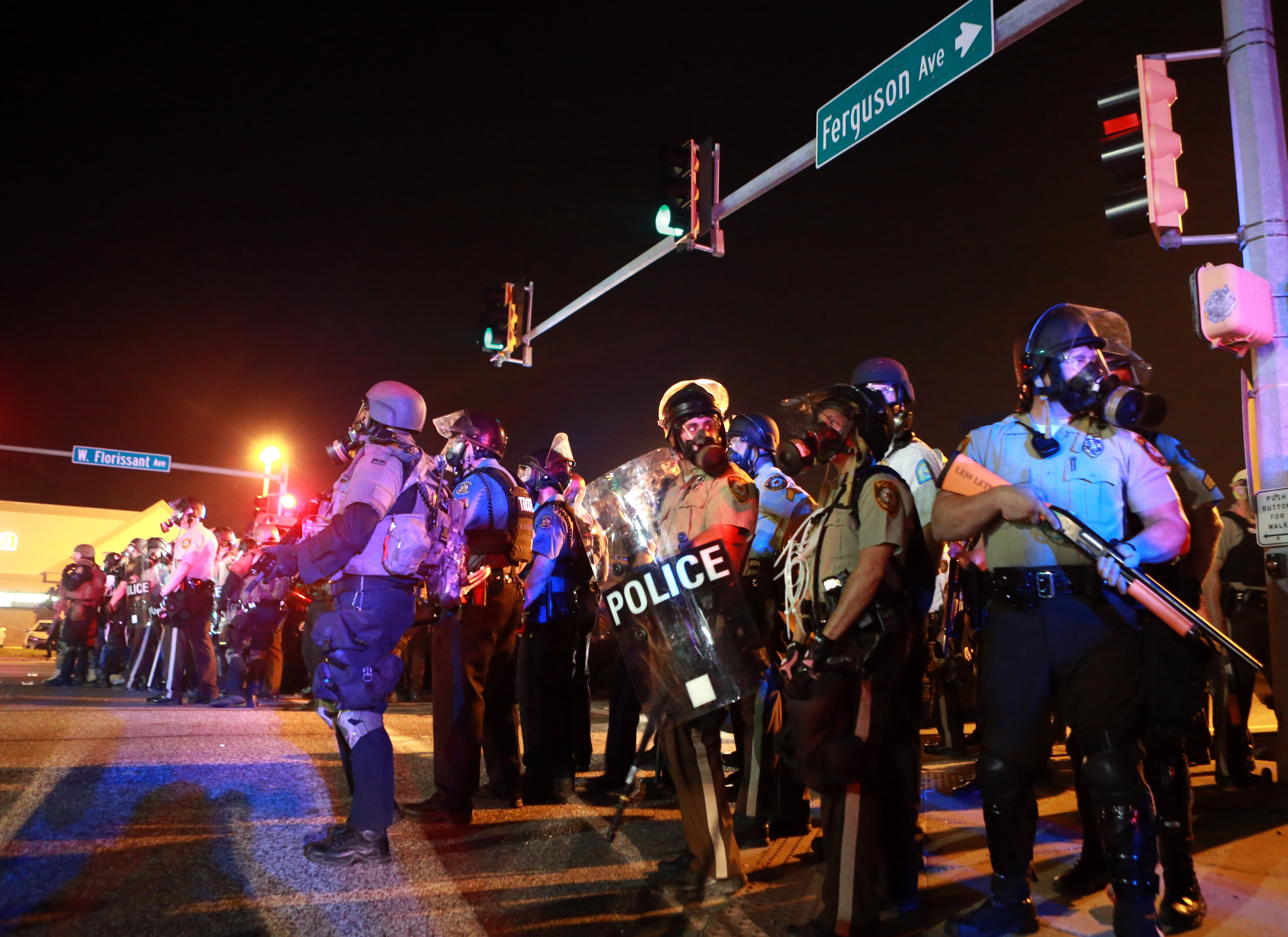 Police stand guard Monday, Aug. 18, 2014, in Ferguson, Mo.