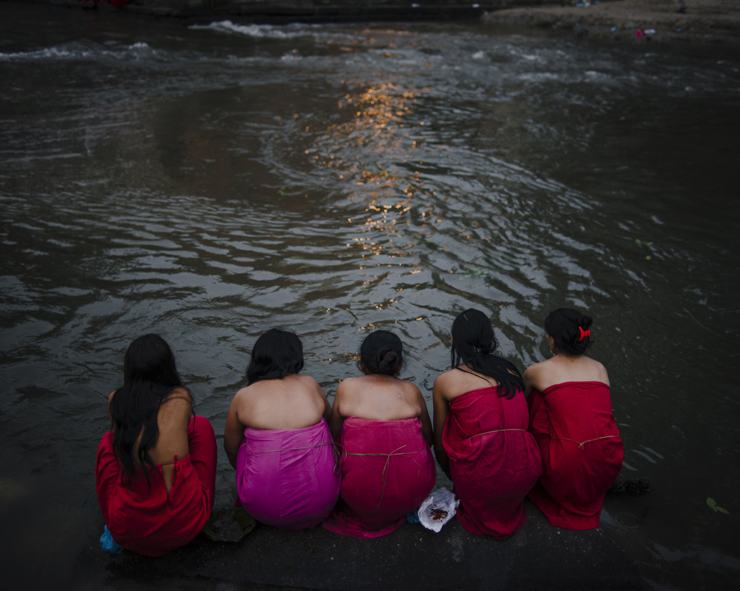 Thousands of women line up at Pashupatinath Temple waters, typically at 3 a.m., ready to atone. They feel they may have touched a man by mistake, and have to do this because their ancestors did so. Kathmandu.