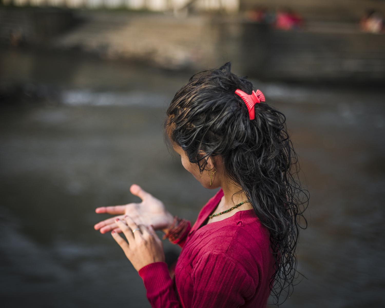 A young girl near the river as she observes Rishi Panchami. Kathmandu.