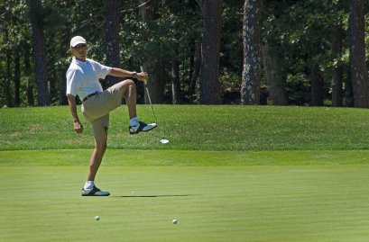 US President Barack Obama reacts to a missed putt on the first green at Farm Neck Golf Club in Oak Bluffs, Mass. on August 11, 2013 during the Obama family vacation to Martha's Vineyard.
