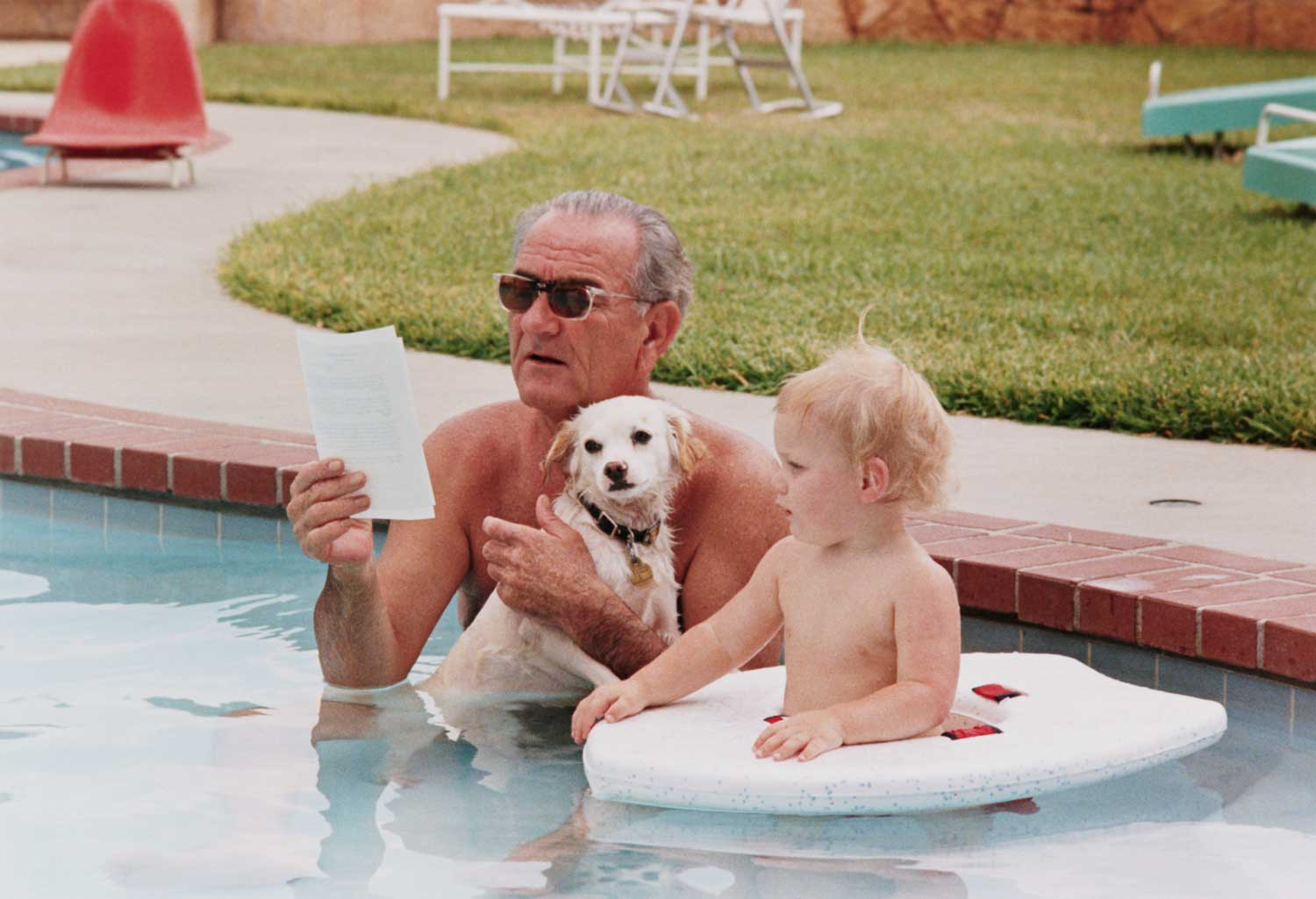 Johnson relaxes in his pool with his grandson Lyn and the First Family's new dog, Yuki, in 1968.