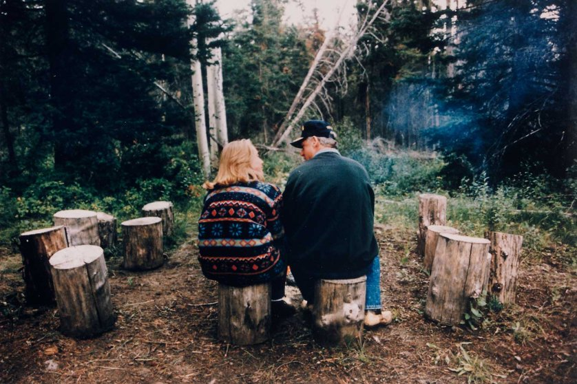 Rear view of Pres. Bill Clinton and First Lady Hillary Rodham Clinton wearing casual clothes and sitting on tree stumps while on vacation.