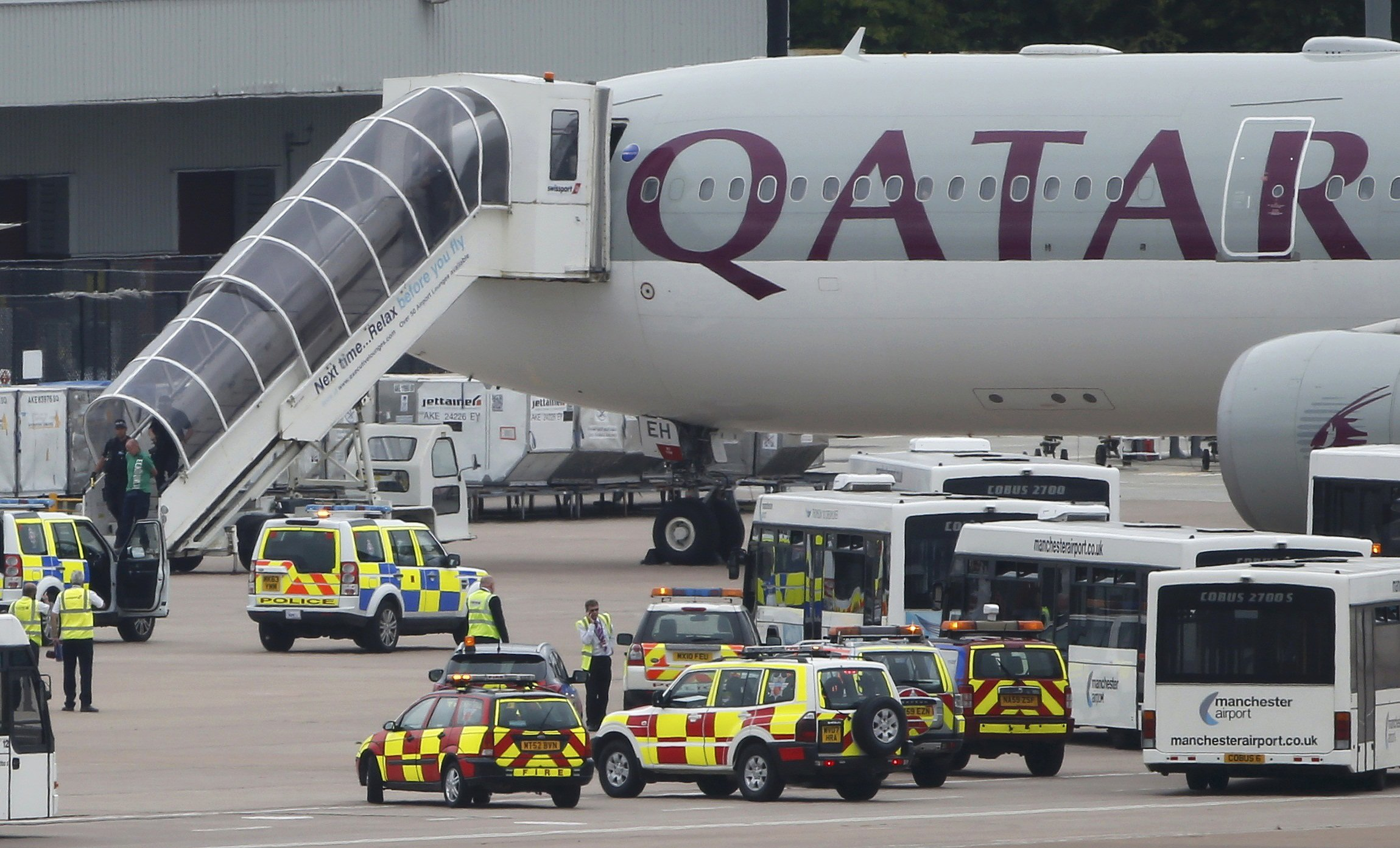 A man is escorted off a Qatar Airways aircraft by police at Manchester airport in Manchester, England on August 5, 2014. A British fighter jet escorted a passenger plane into Manchester airport on Tuesday after the pilot reported that a suspect device was possibly on board.
