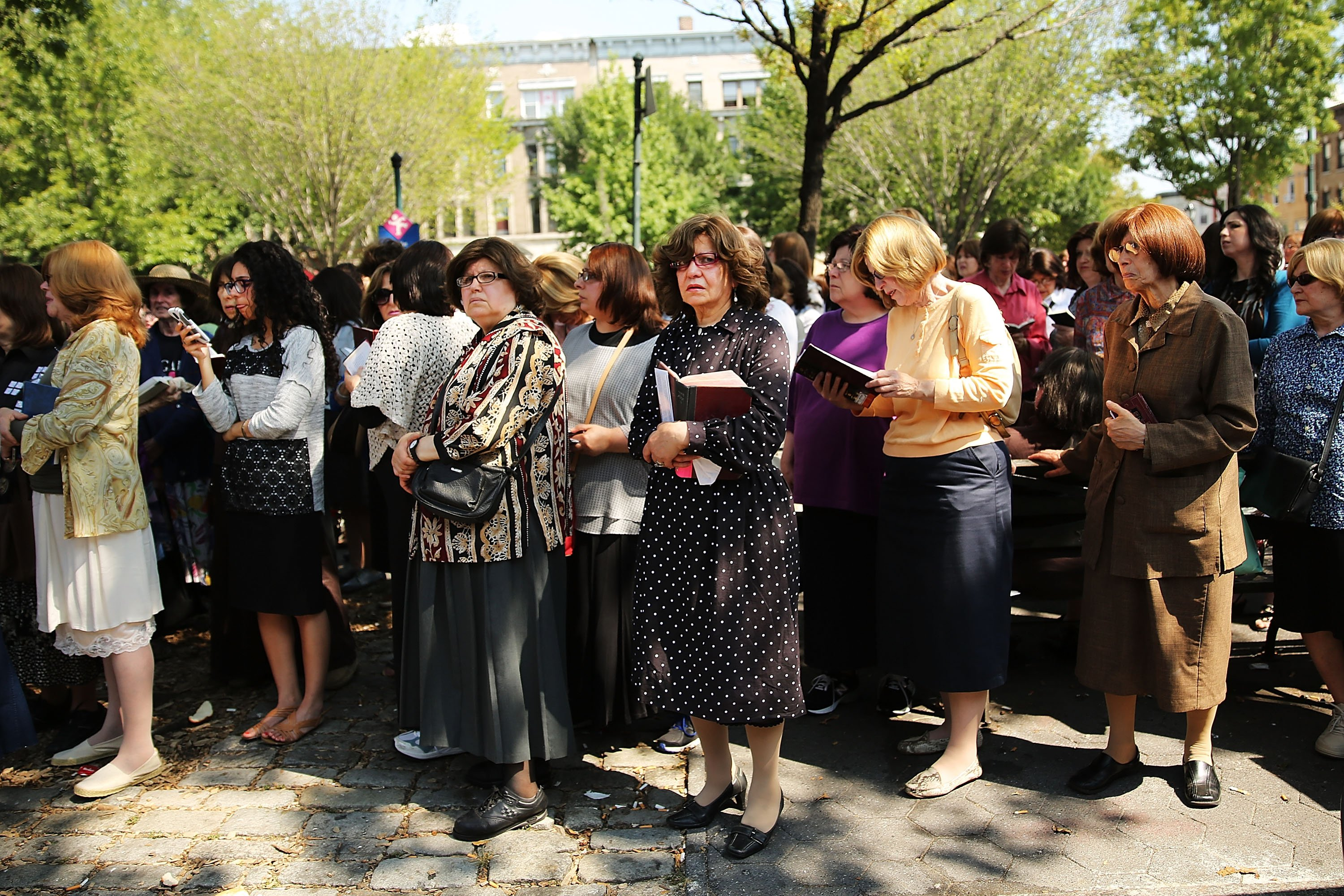 Women watch as mourners pay their respects to the coffin in a hearse outside the Chabad-Lubavitch headquarters during the funeral of Rabbi Joseph Raksin in the Brooklyn borough of New York City on Aug. 11, 2014.