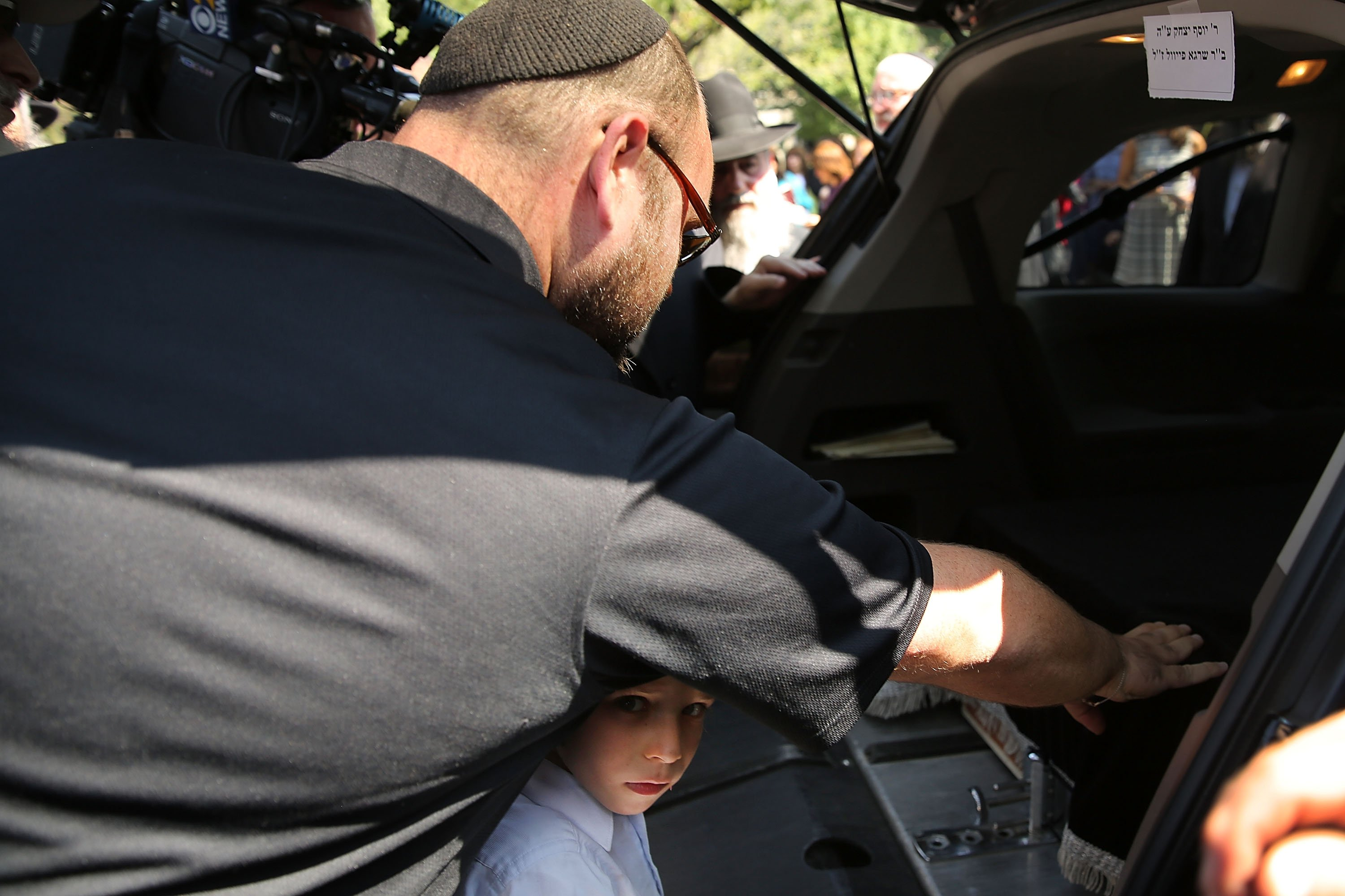A child looks on as mourners pay their respects to the coffin in a hearse outside the Chabad-Lubavitch headquarters during the funeral of Rabbi Joseph Raksin in the Brooklyn borough of New York City on Aug. 11, 2014.