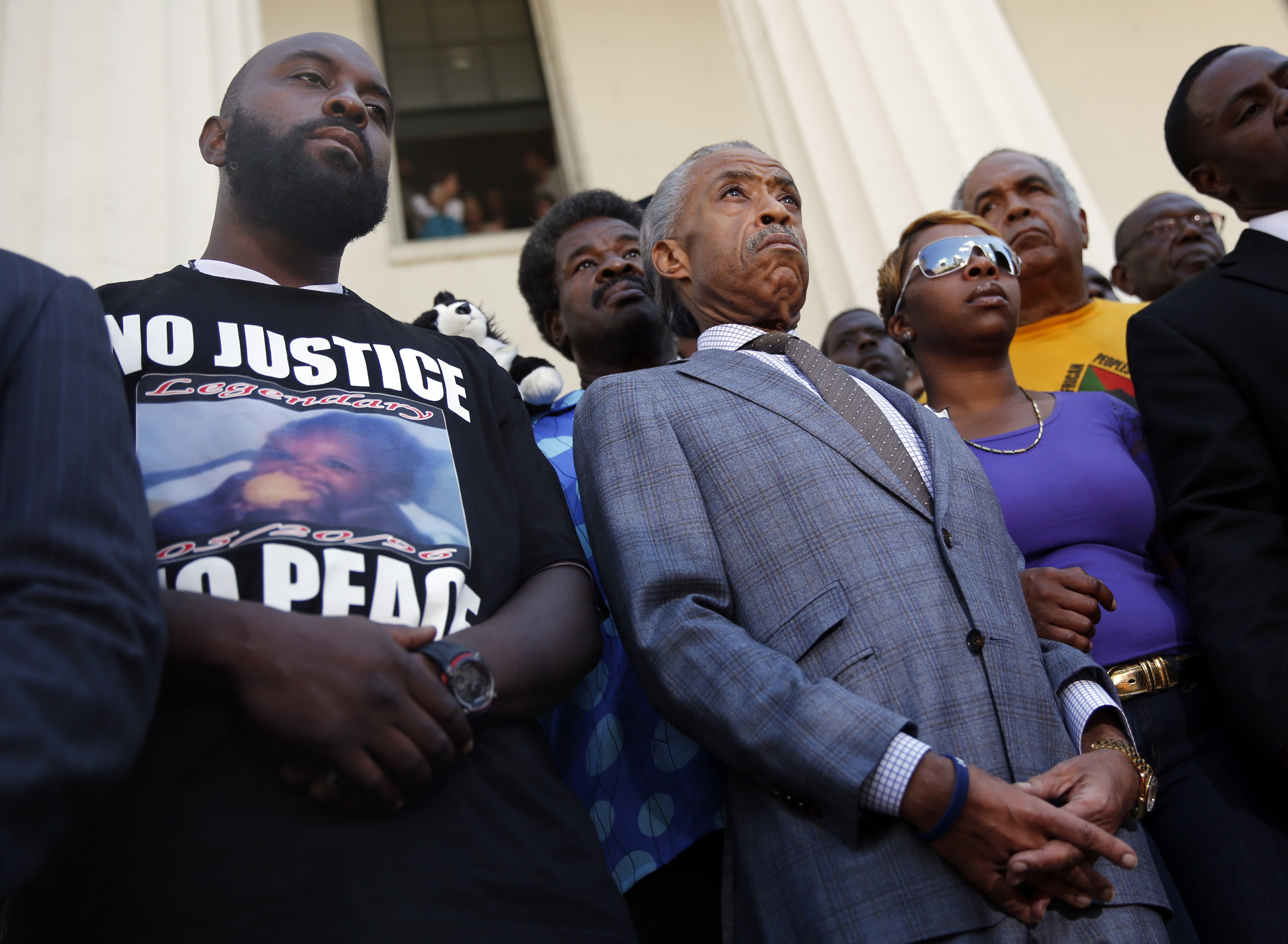 From left: Michael Brown, Sr., Reverend Al Sharpton, and Lesley McSpadden during a news conference outside the Old Courthouse in St. Louis on Aug. 12, 2014.