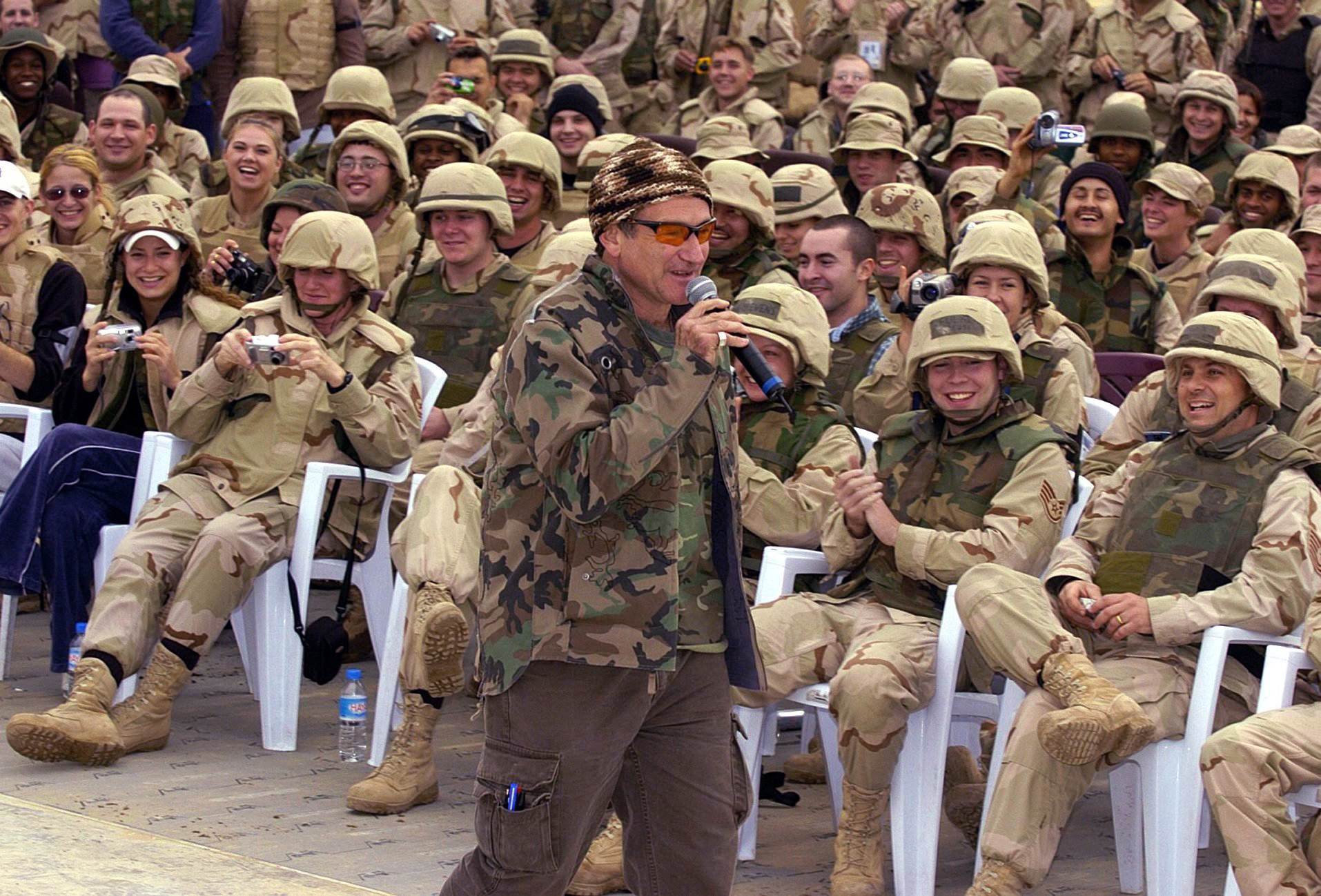 Robin Williams wears a camouflage jacket while entertaining a cheering crowd of US troops as part of a United Service Organiztions (USO) Holiday Tour at the International Airport in Baghdad, Dec. 16, 2003.