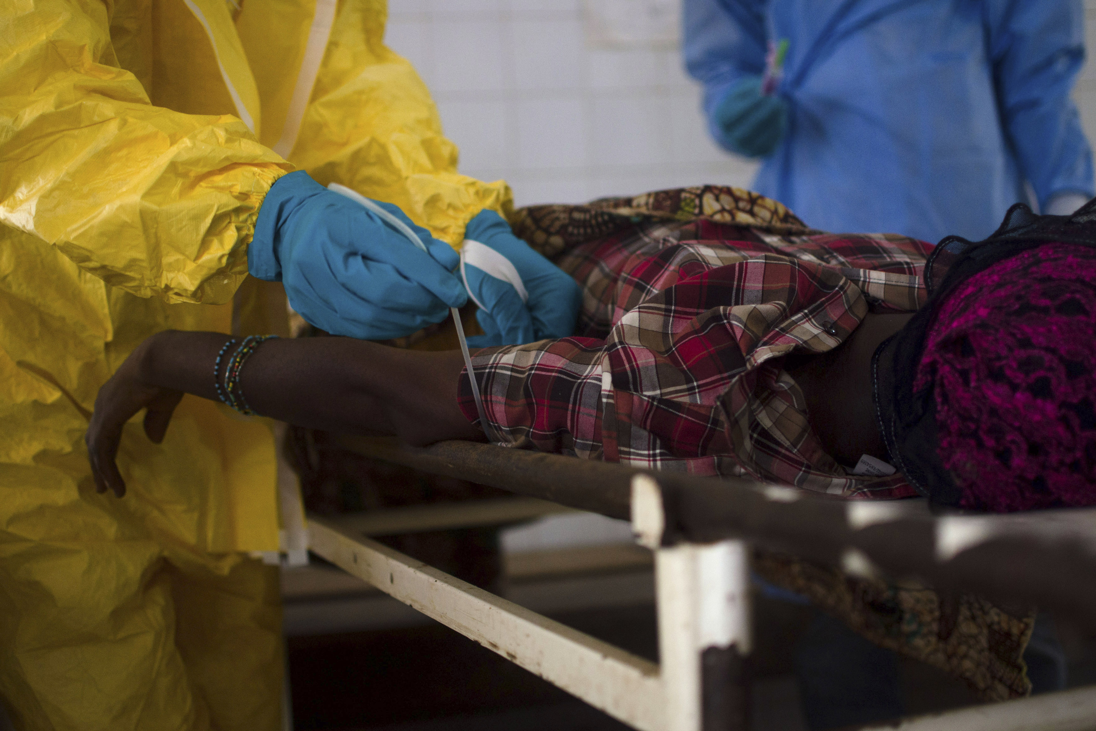 Medical staff take a blood sample from a suspected Ebola patient at the government hospital in Kenema, Sierra Leone, on July 10, 2014