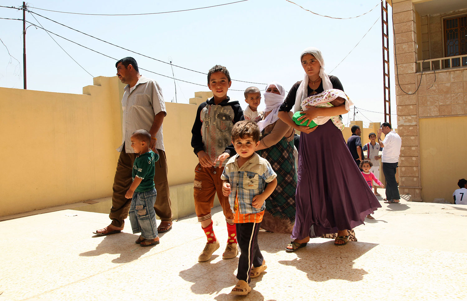 Displaced families from the minority Yazidi sect, fleeing the violence in the Iraqi town of Sinjar, west of Mosul, arrive at Dohuk province, Aug. 4, 2014