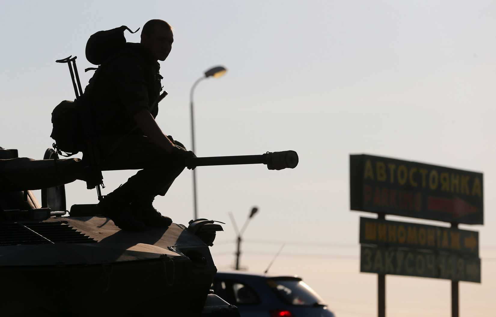 A Russian serviceman sits atop an armored vehicle outside Kamensk-Shakhtinsky, Russia's Rostov region, on Aug. 15, 2014. Dozens of heavy Russian military vehicles amassed on Friday near the border with Ukraine where a huge Russian convoy with humanitarian aid came to a halt as Moscow and Kiev struggled to agree border crossing procedures