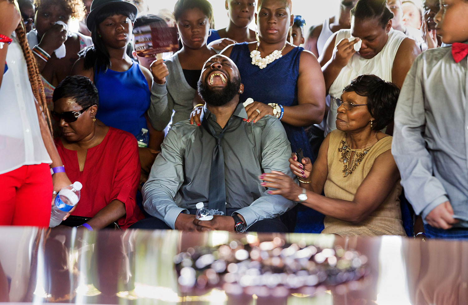 Michael Brown Sr., center, yells out as his son's casket is lowered into the ground at St. Peter's Cemetery in St. Louis on Aug. 25, 2014