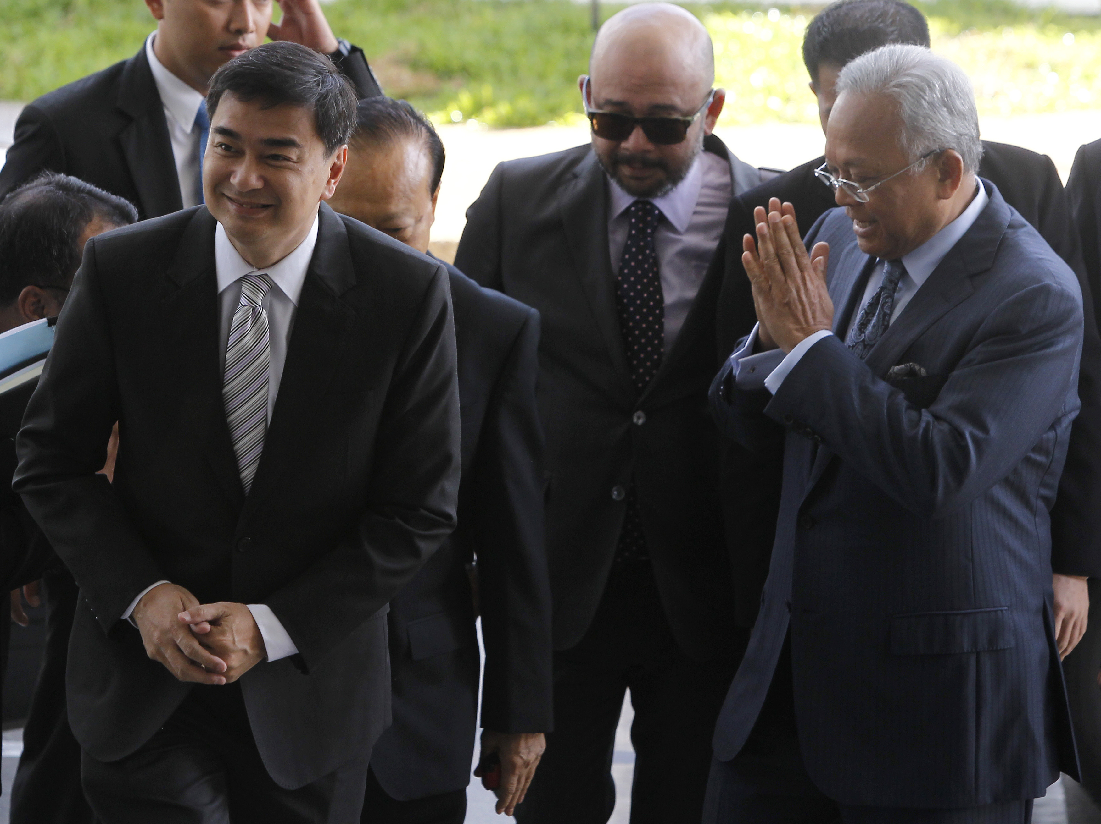 Former Thai Prime Minister Abhisit Vejjajiva, left, and his then deputy Suthep Thaugsuban arrive at the Department of Special Investigation in Bangkok on May 14, 2013.
