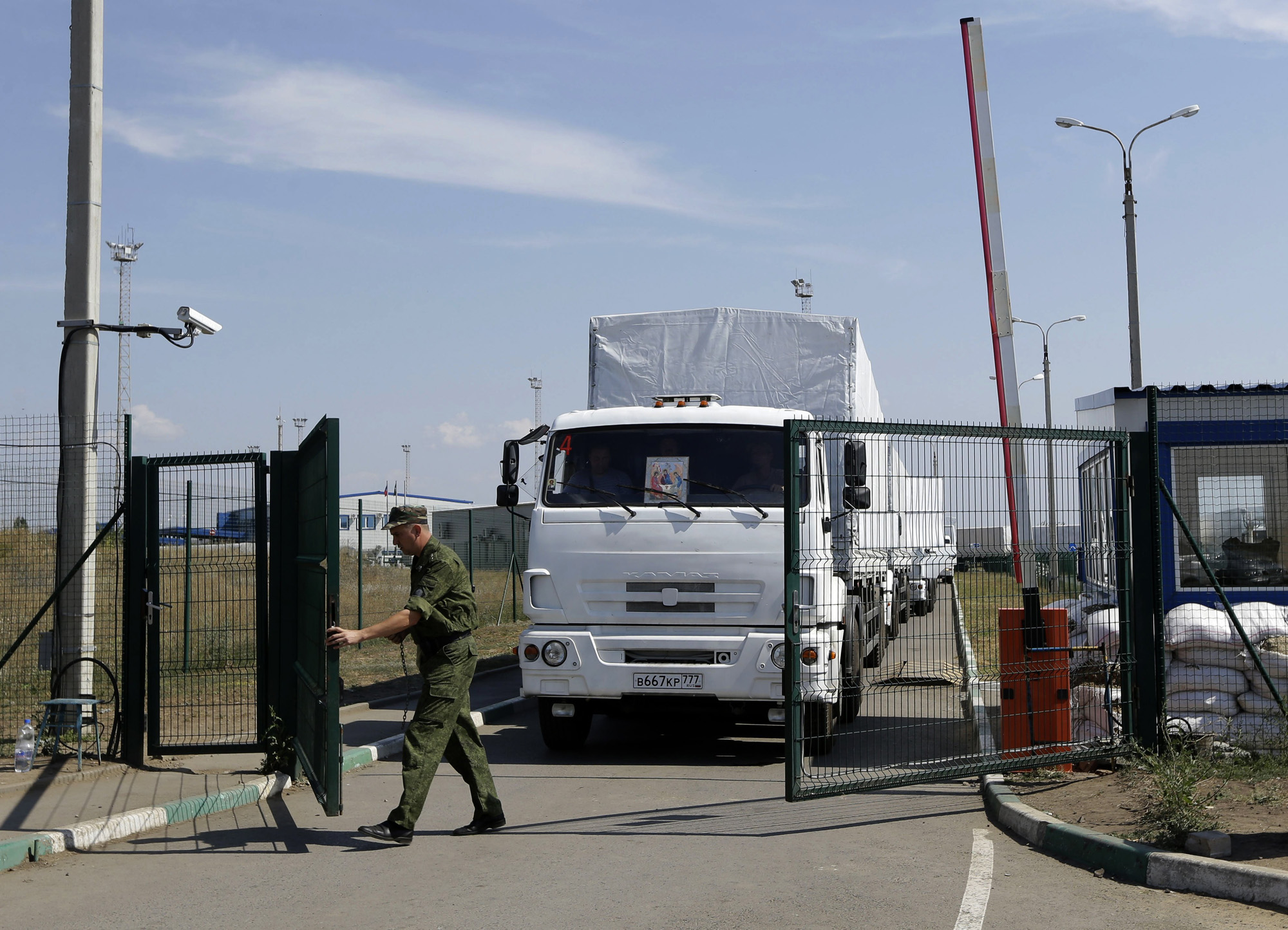 A Russian border guard opens a gate into the Ukraine for the first trucks heading into the country from the Russian town of Donetsk, Rostov-on-Don region, Russia,  Aug. 22, 2014.
