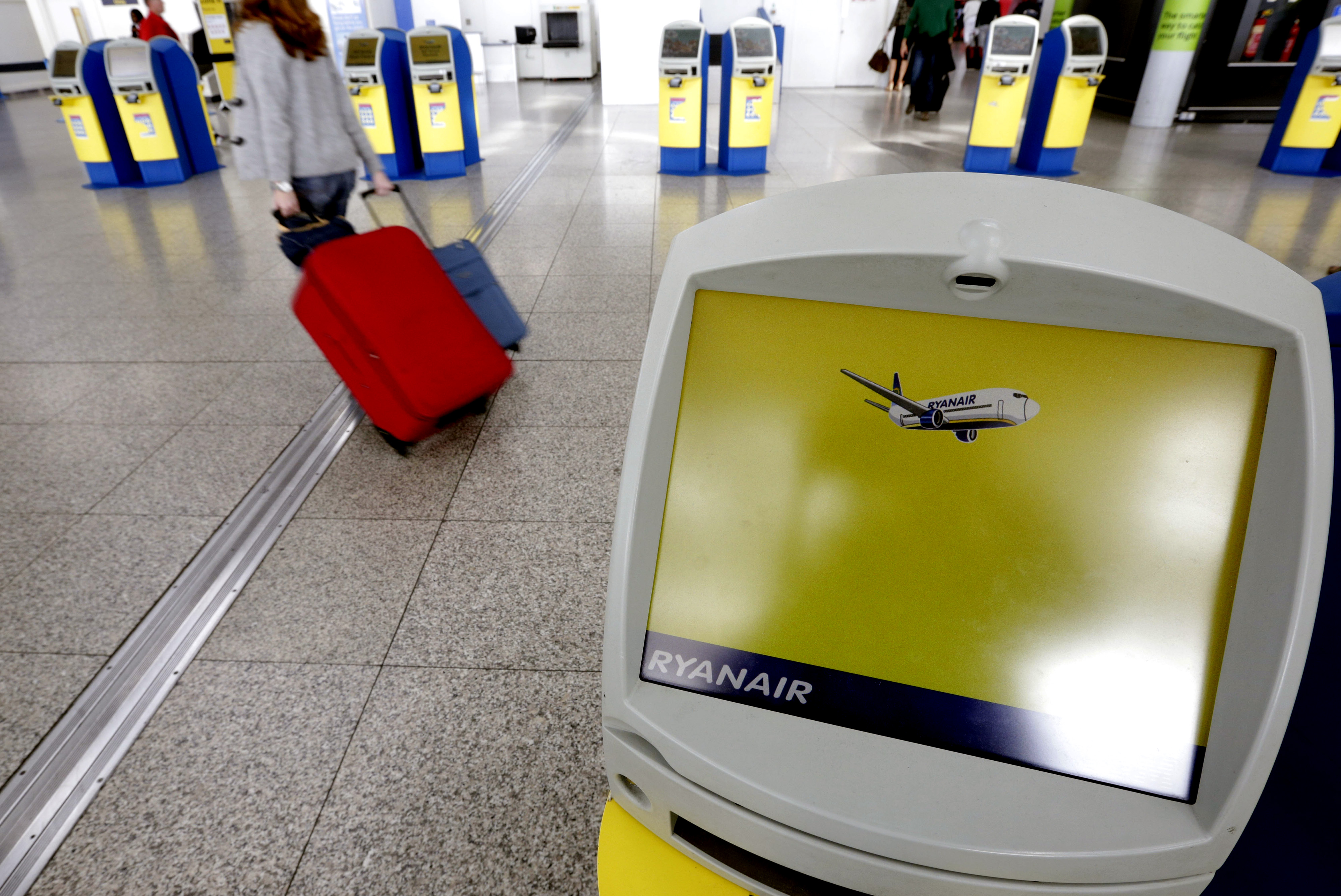 A passenger passes self-service check-in machines Ryanair Holdings Plc at Stansted Airport in London, U.K., on Wednesday, Aug. 7, 2013.