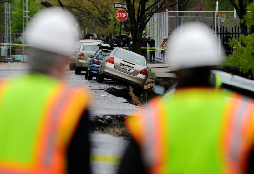 Emergency officials approach cars on the edge of a sinkhole in Baltimore, April 30, 2014.