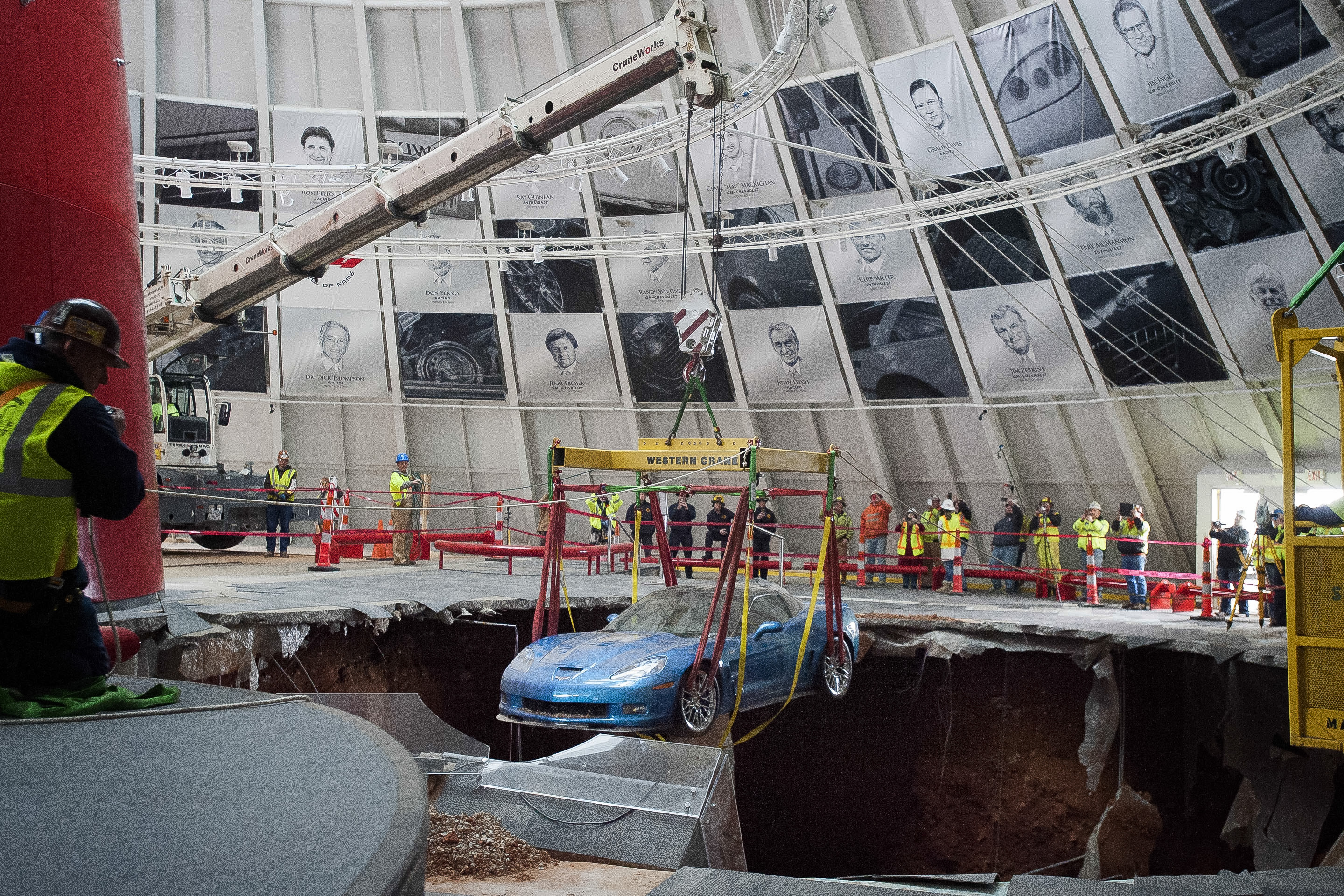 One of eight Chevrolet Corvettes is removed from a sinkhole in the Skydome at the National Corvette Museum, Monday, March. 3, 2014, in Bowling Green, Ky.  On Feb. 12 2014, a large sinkhole swallowed eight prized cars, piling them in a heap amid loose dirt and concrete fragments.
