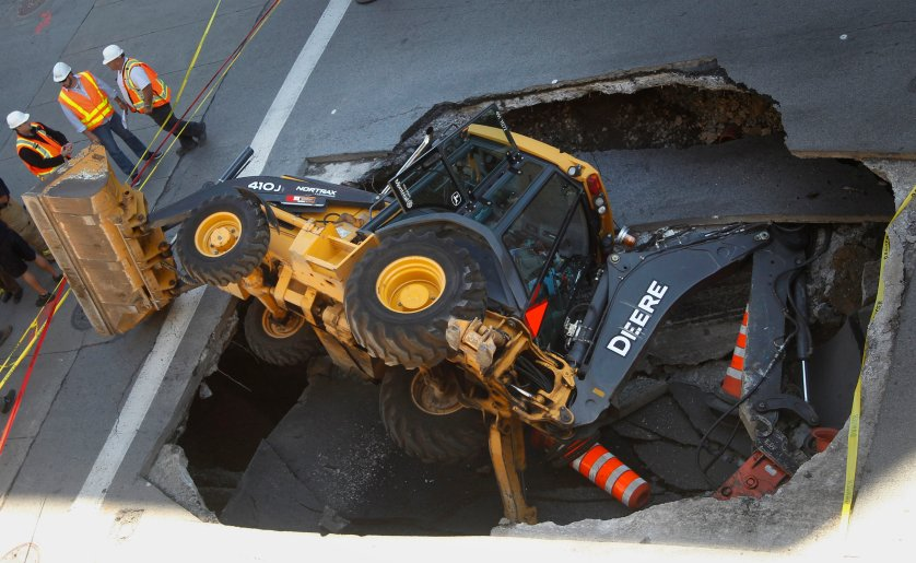 A construction vehicle lies where it was swallowed by a sinkhole on Saint-Catherine Street in downtown Montreal