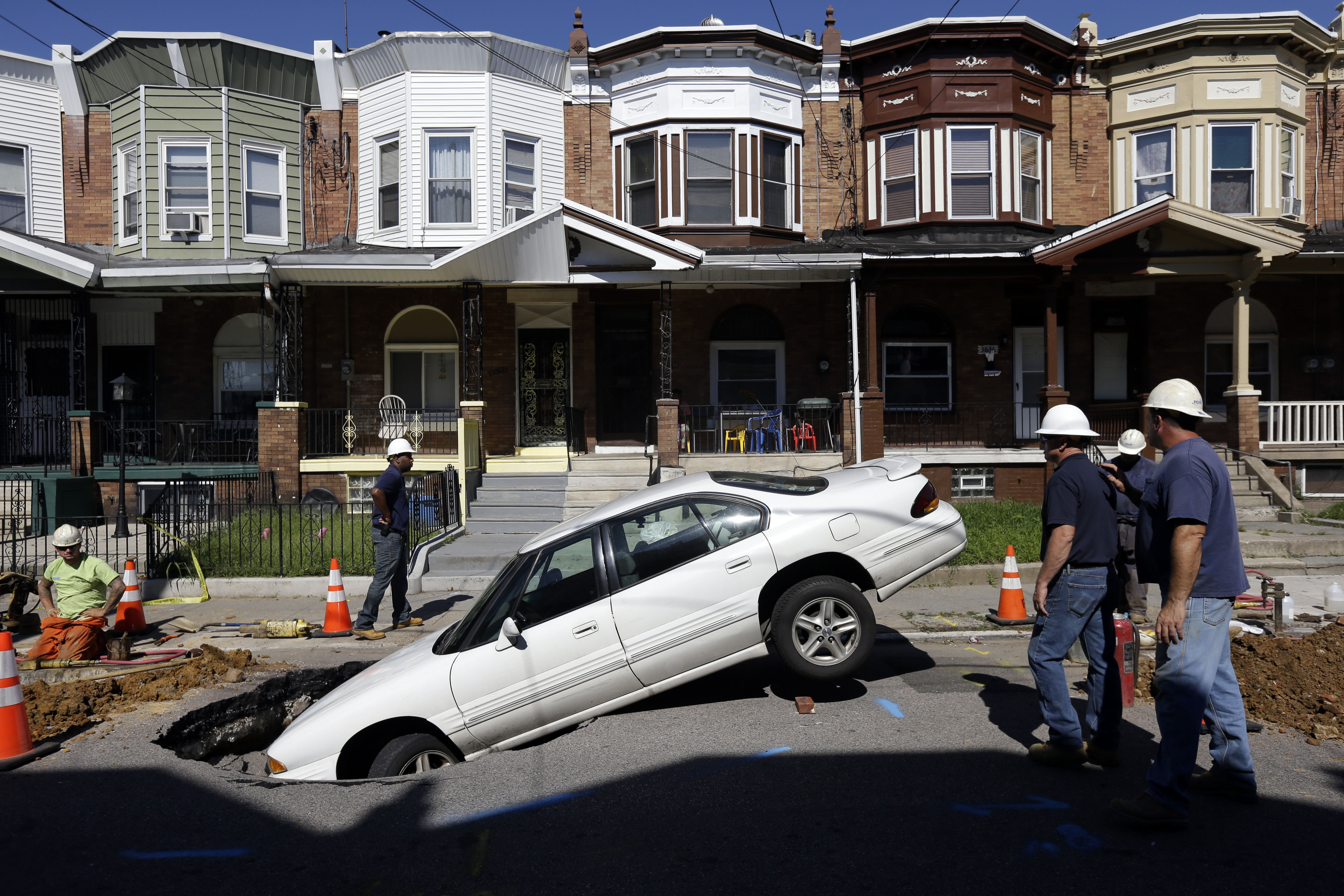Workmen view a car with its front end in a sinkhole, July 30, 2013, in Philadelphia. PVI-TV reported the sinkhole opened up overnight on a street in the city's Hunting Park section, with the front of the car falling in the hole.