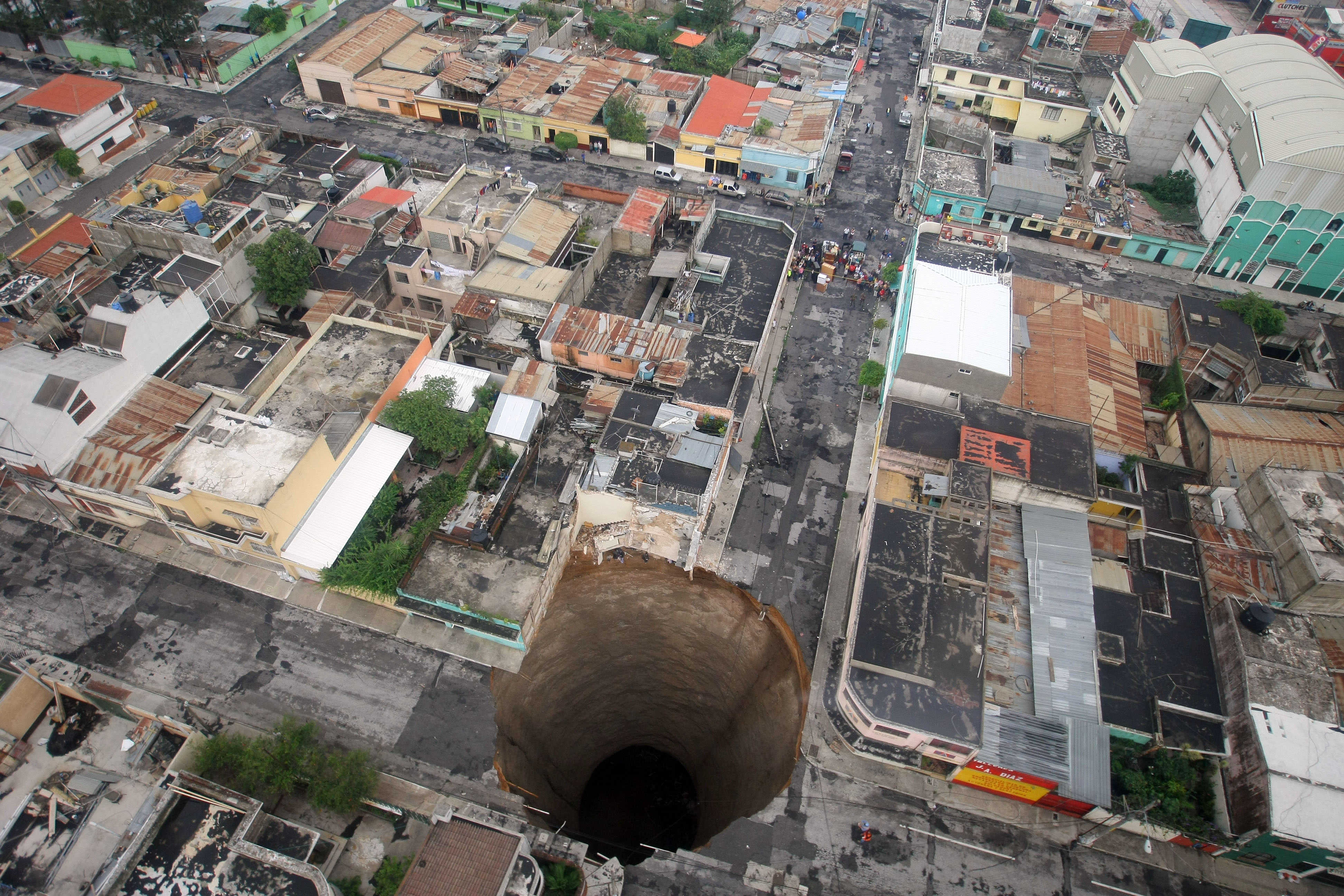 A sinkhole covers a street intersection in downtown Guatemala City, May 31, 2010. A day earlier authorities blamed the heavy rains caused by tropical storm Agatha as the cause of the crater that swallowed a a three-story building but now say they will be conducting further studies to determine the cause.