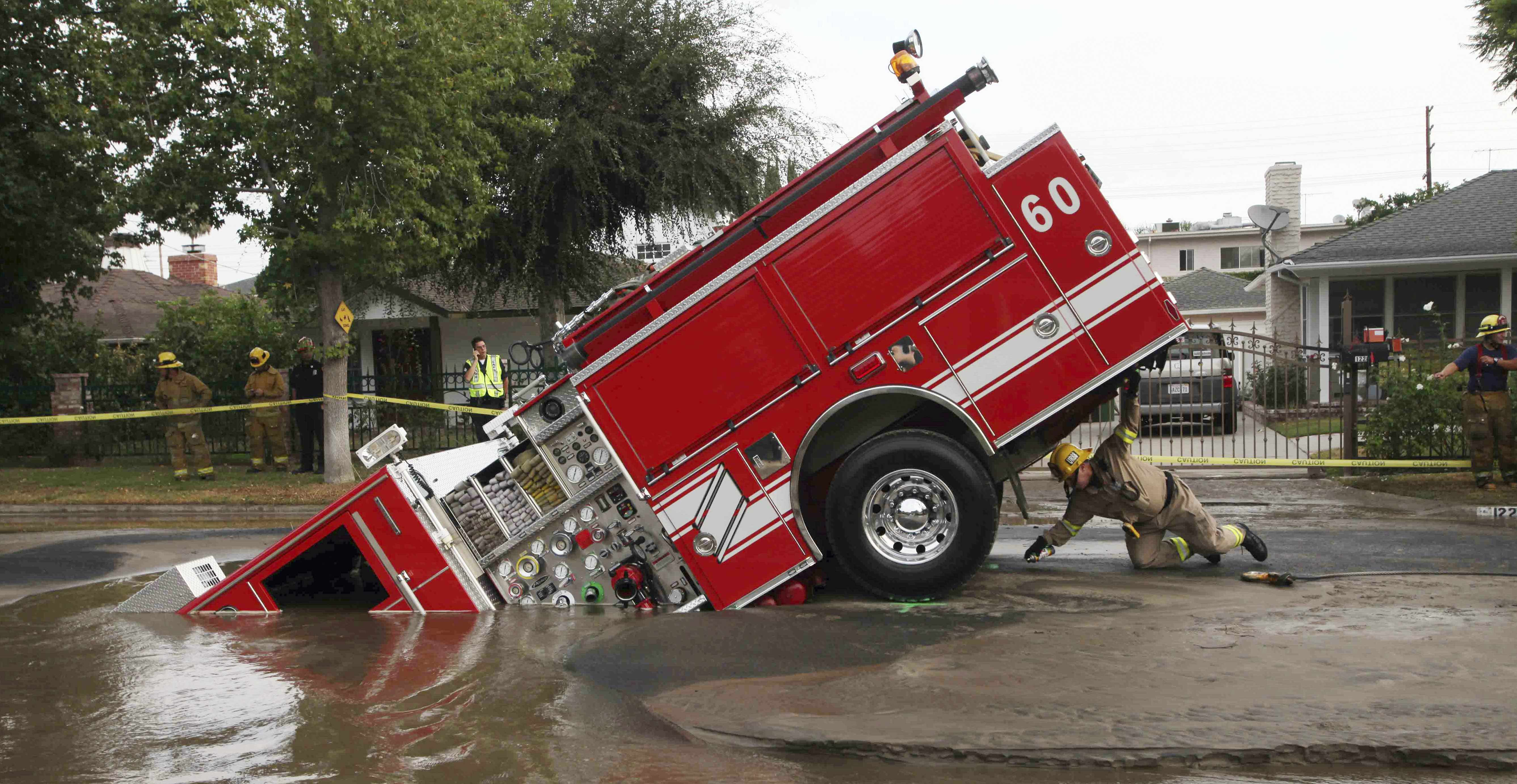 A Los Angeles fireman looks under a fire truck stuck in a sinkhole in the Valley Village neighborhood of Los Angeles, Sept. 8, 2009. Four firefighters escaped injury early Tuesday after their fire engine sunk into a large hole caused by a burst water main in the San Fernando Valley, authorities said.
