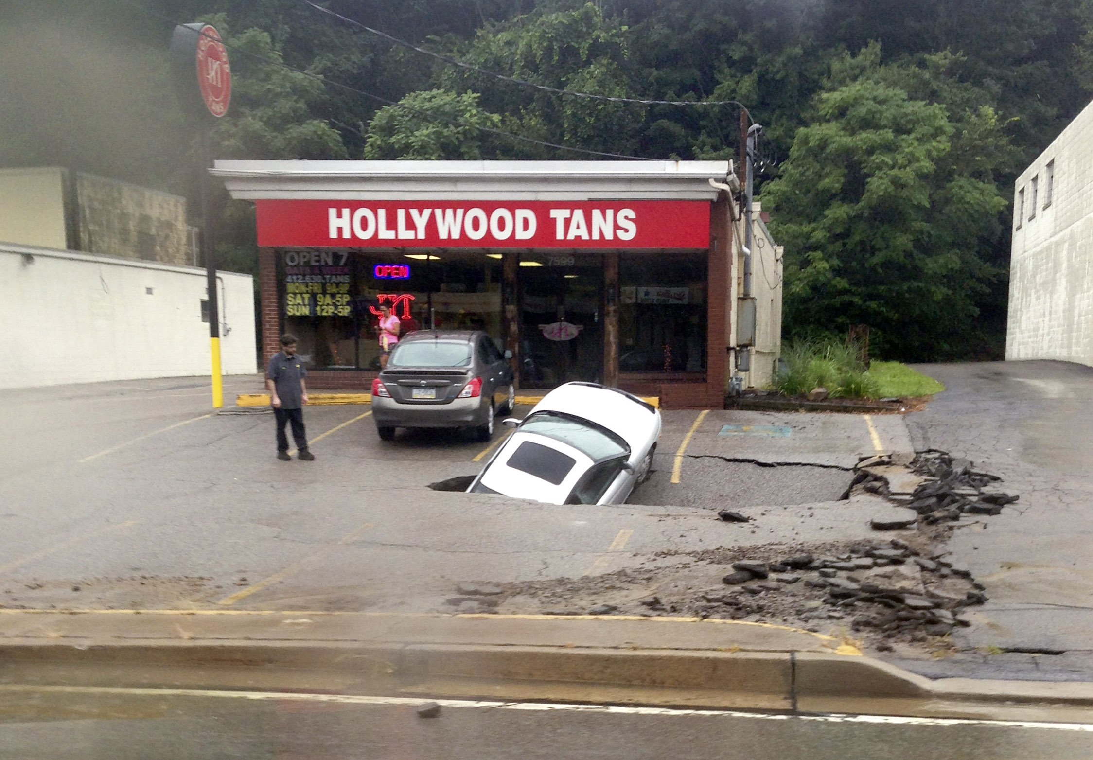 A man looks at a car as it falls into a sinkhole on McKnight Road in Ross Township of Pittsburgh on Aug. 12, 2014.