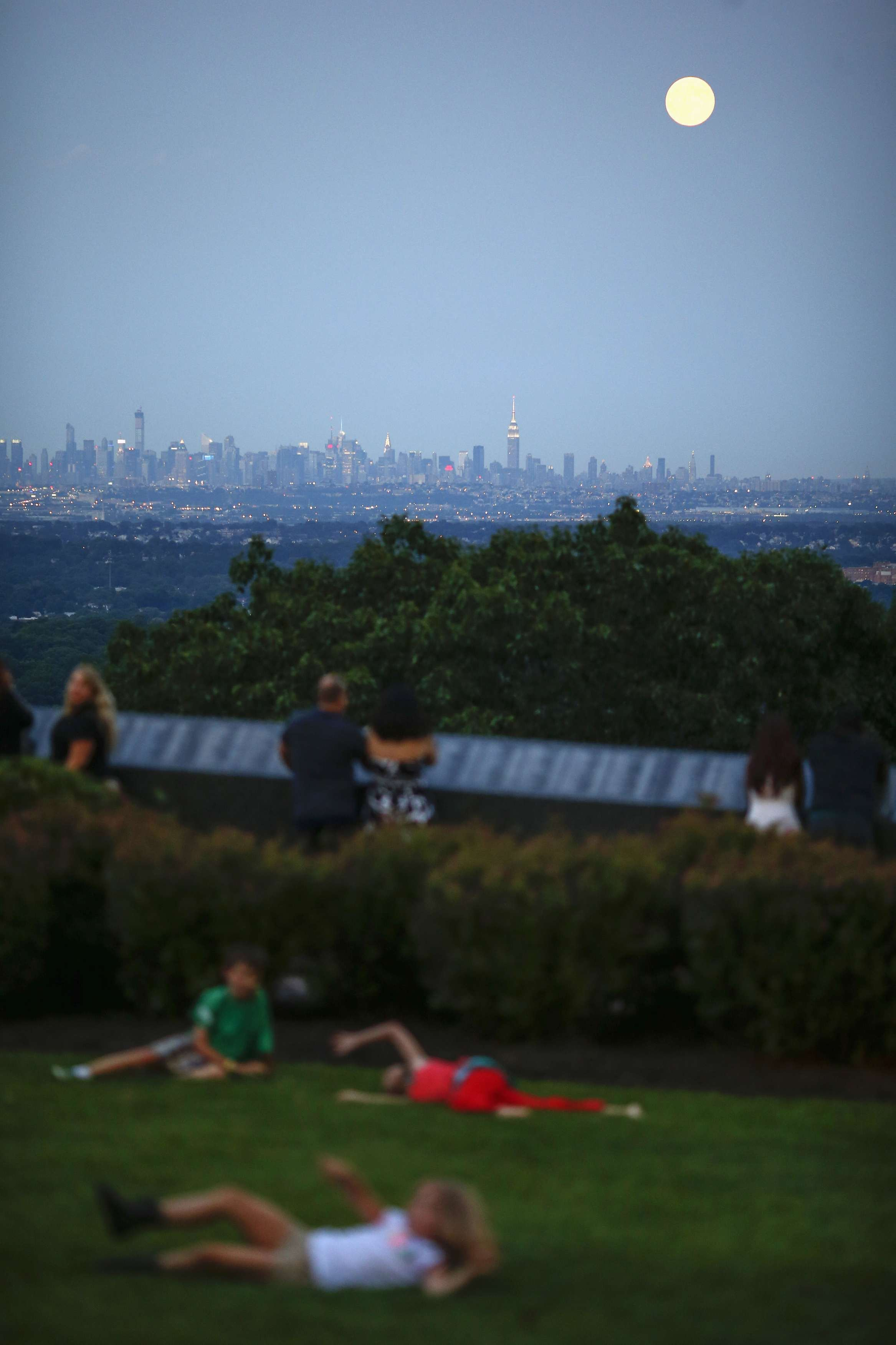 Children play on the grass while a full moon known as  supermoon  rises over the skyline of New York and the Empire State Building, as seen from the Eagle Rock Reservation in West Orange, New Jersey on August 10, 2014.