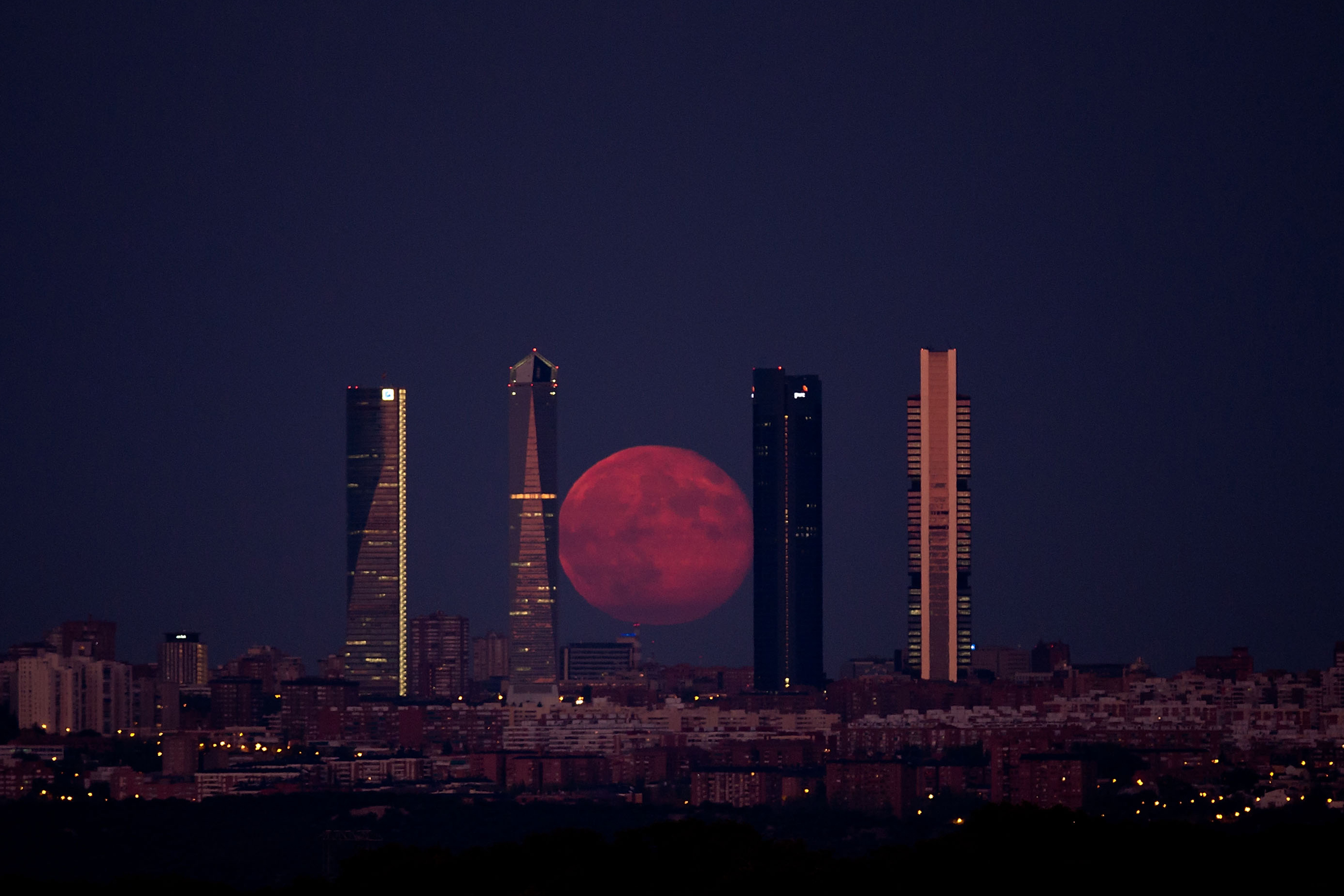 The moon shines through the Four Towers Madrid skyscrapers on August 11, 2014 in Madrid, Spain.