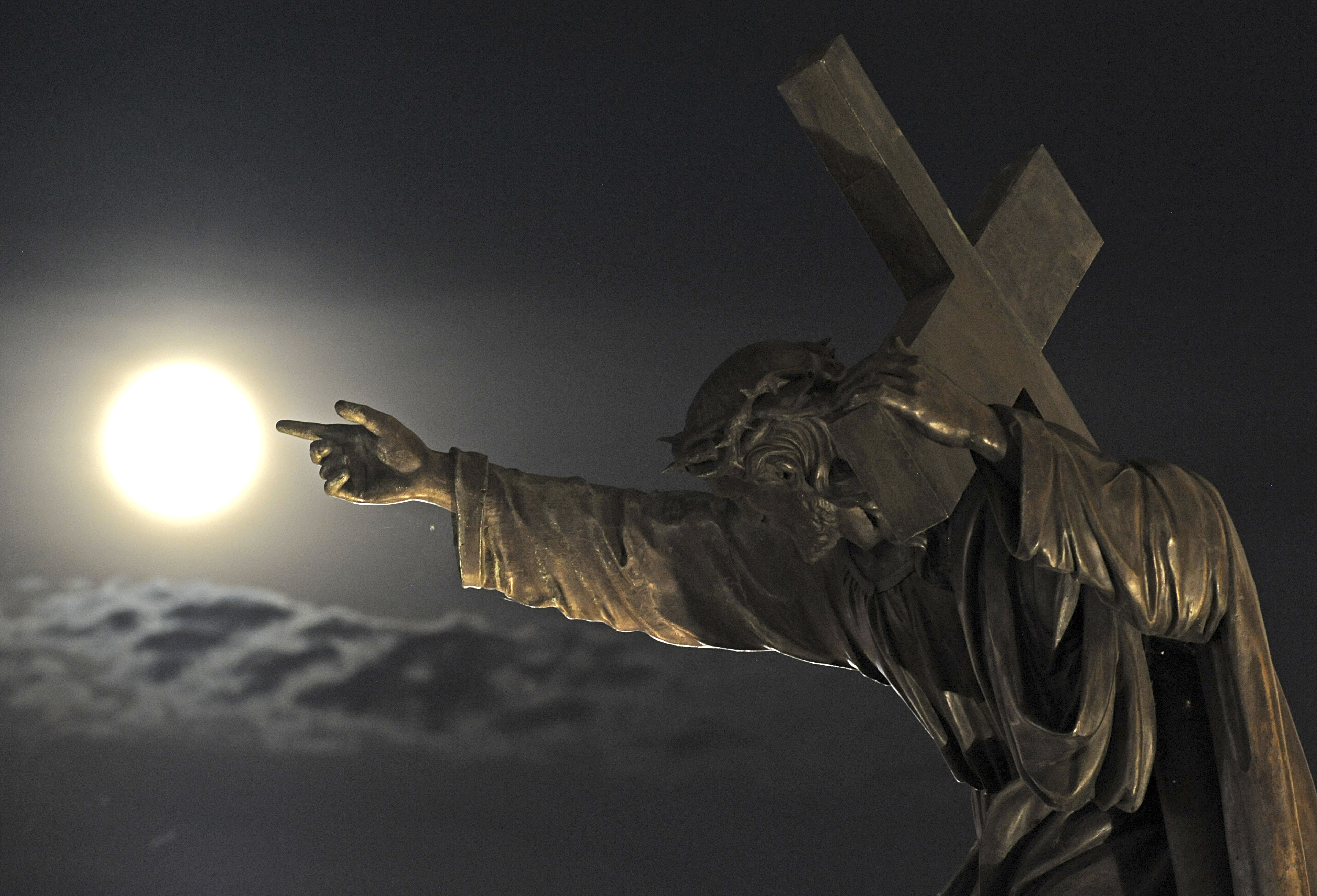 A supermoon rises above a Jesus Christ statue in front of the Holy Cross church  in Warsaw, Poland on August 10, 2014.
