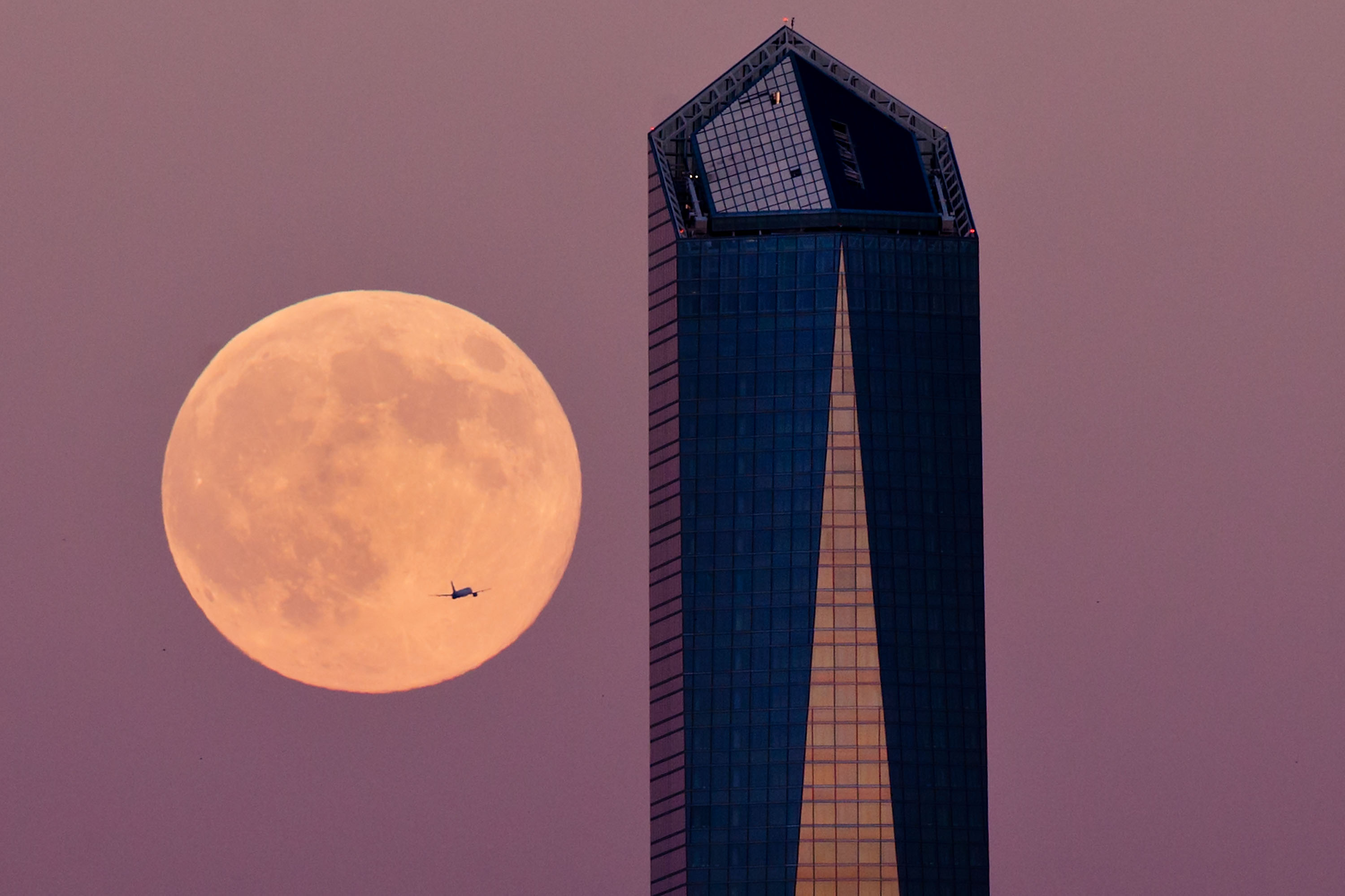 A plane flys across the supermoon surrounded by a Madrid skyscraper on August 9, 2014 in Madrid.