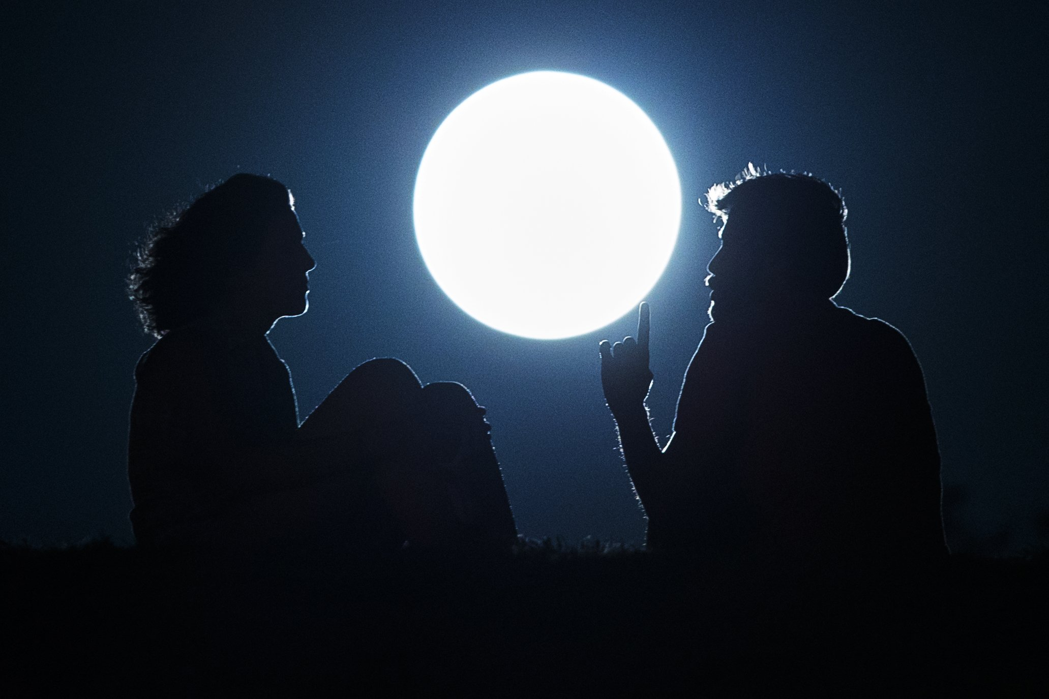 A couple talk as they sit against  the perigee moon, also known as a supermoon, in Madrid on August 10, 2014.