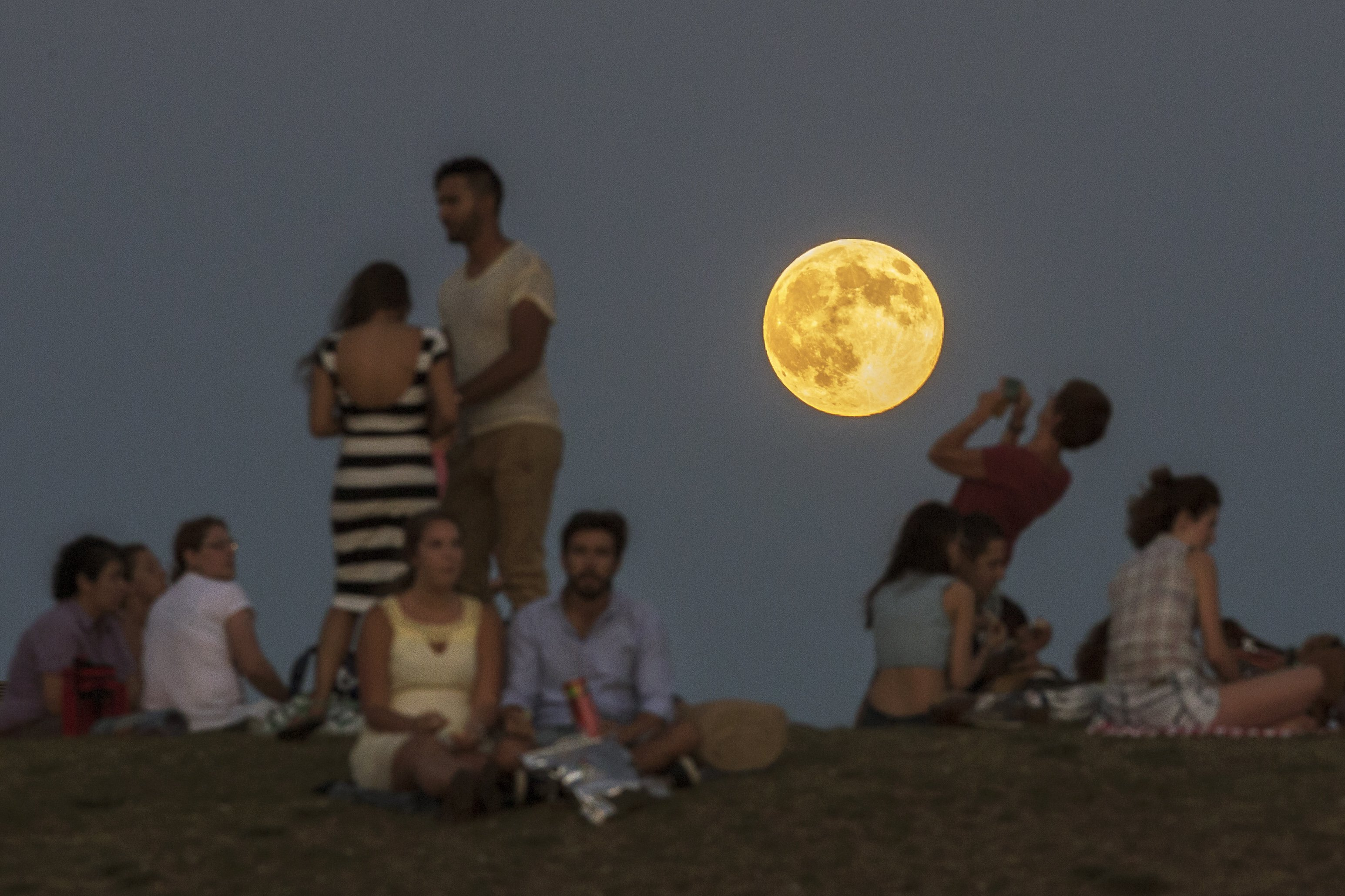 People gather in the park as a perigee moon, also known as a supermoon, rises in Madrid on August, 10, 2014.