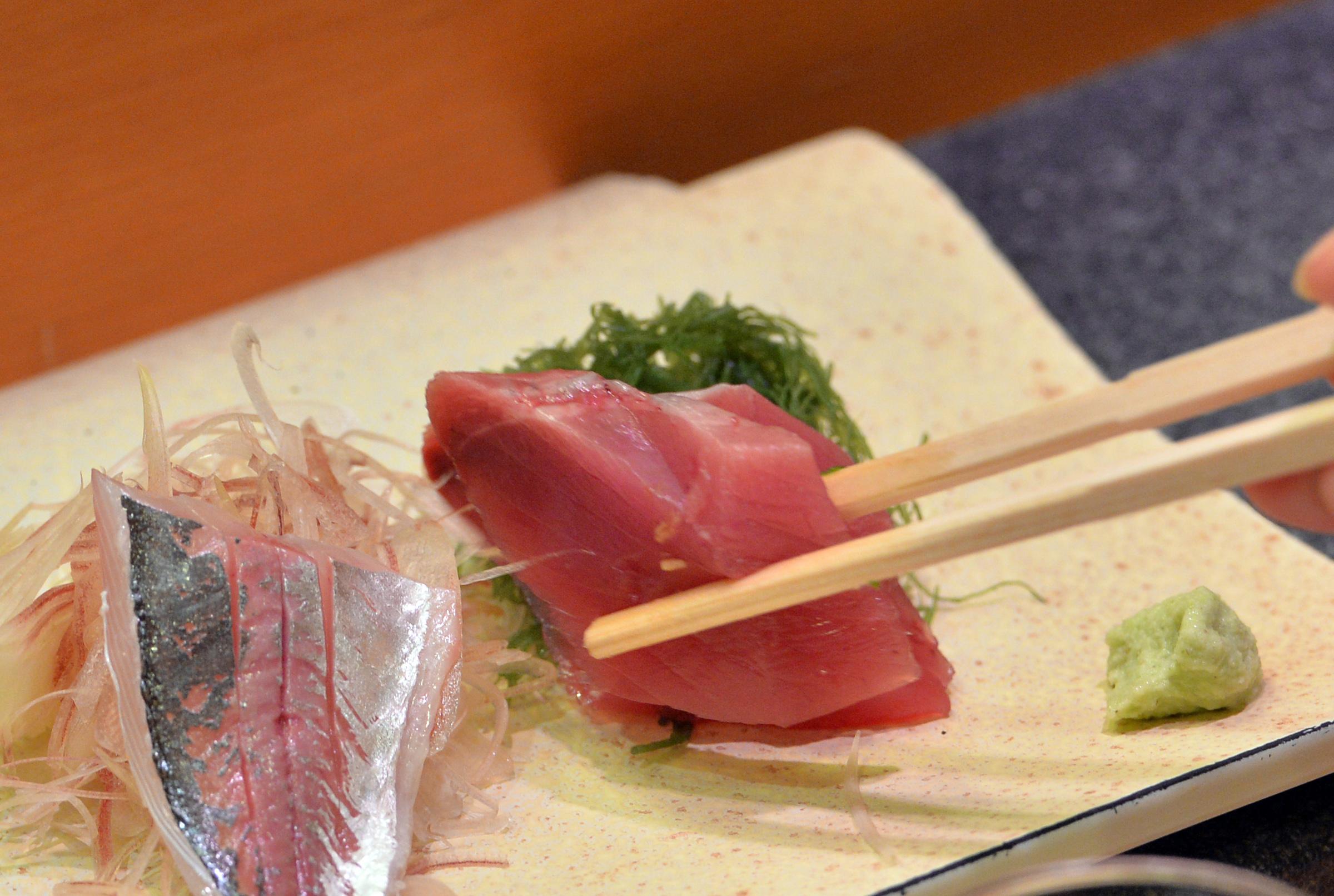 A customer eats bonito and horse mackerel sashimi (raw fish) at a high-end sushi restaurant in Tokyo on  July 16, 2013.