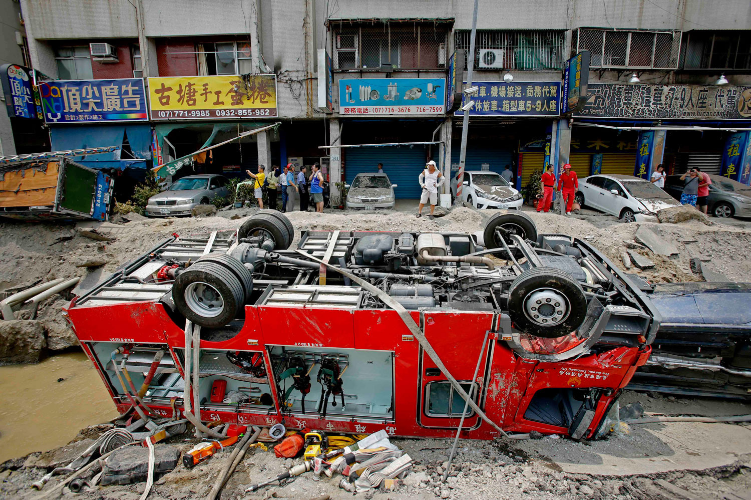 A destroyed fire truck is seen overturned in the rubble after massive gas explosions in Kaohsiung, Taiwan, Friday, Aug. 1, 2014. A series of underground explosions about midnight Thursday and early Friday ripped through Taiwan's second-largest city, killing scores of people, Taiwan's National Fire Agency said.