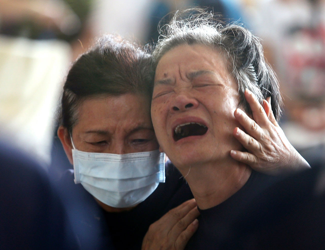 Relatives of the victims cry after an explosion in Kaohsiung, southern Taiwan on Aug. 1, 2014.