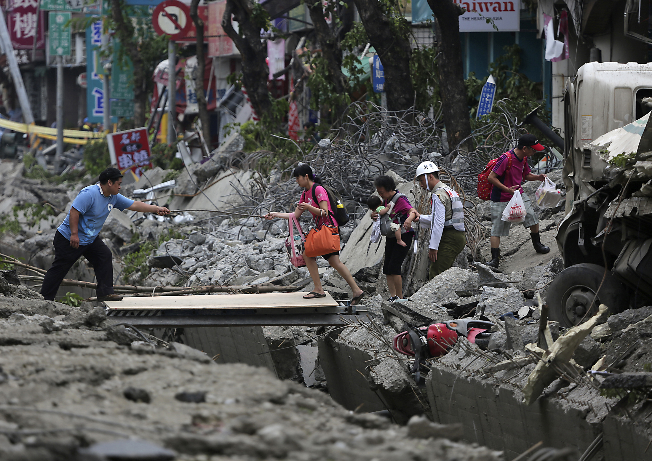 People walk across a gap caused by an explosion in Kaohsiung, southern Taiwan on Aug. 1, 2014.
