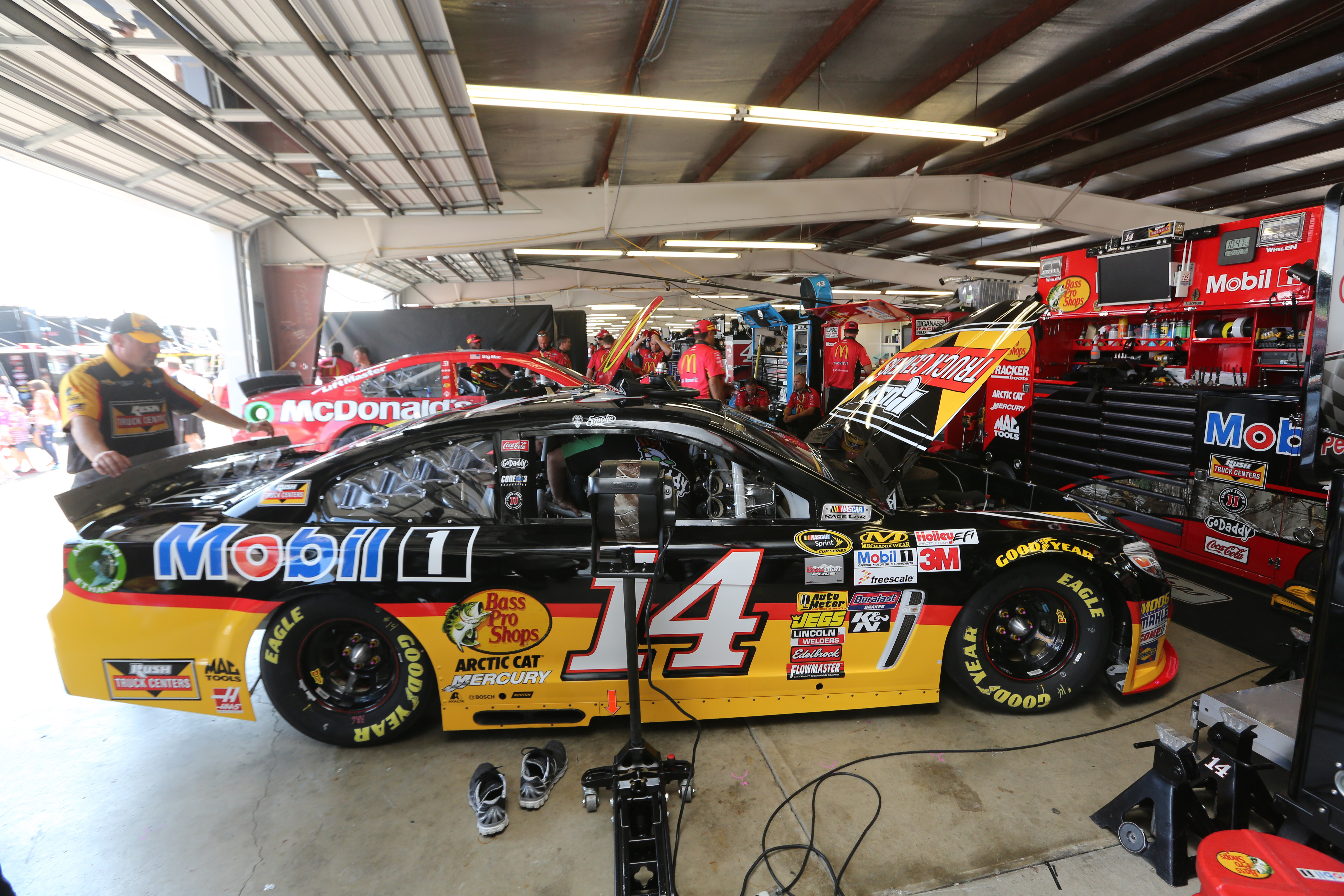 The #14 Rush Truck Centers/Mobil 1 Chevrolet is prepared by its crew in the garage area prior to the NASCAR Sprint Cup Series Cheez-It 355 at Watkins Glen International on August 10, 2014 in Watkins Glen, New York.