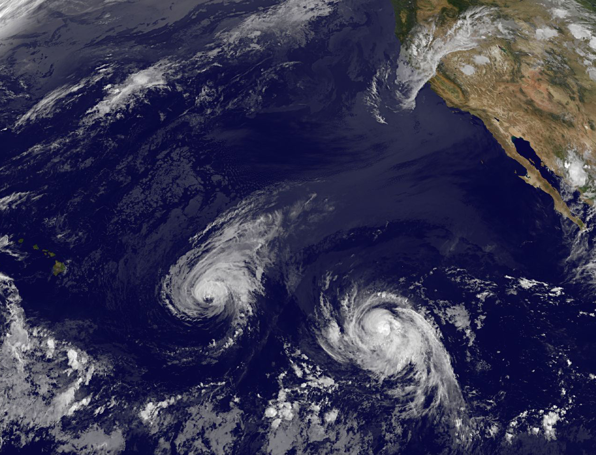 This image provided by NOAA taken Wednesday, Aug. 6, 2014, shows Hurricane Iselle, center, and Hurricane Julio, right.