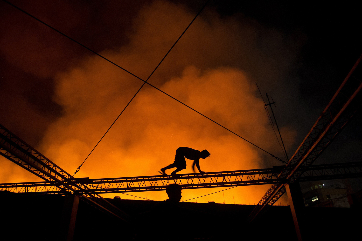 Aug. 26, 2014. A man crawls on a truss of a building to witness a fire that engulfed a warehouse in Manila.