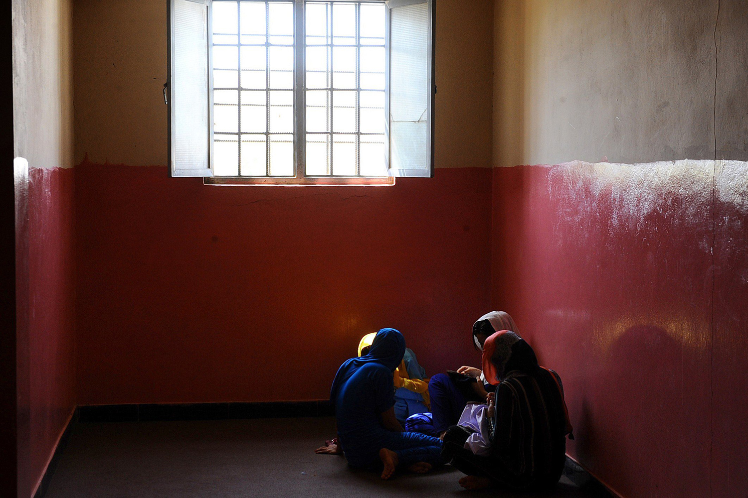 Aug. 27, 2014. Female Afghan prisoners gather in a group inside the female prison in Herat. The facility, which was built by the Italian Provincial Reconstruction Team, holds approximately 140 inmates, some with their children alongside them, whose crimes range from murder, drug trafficking to running away from home.
