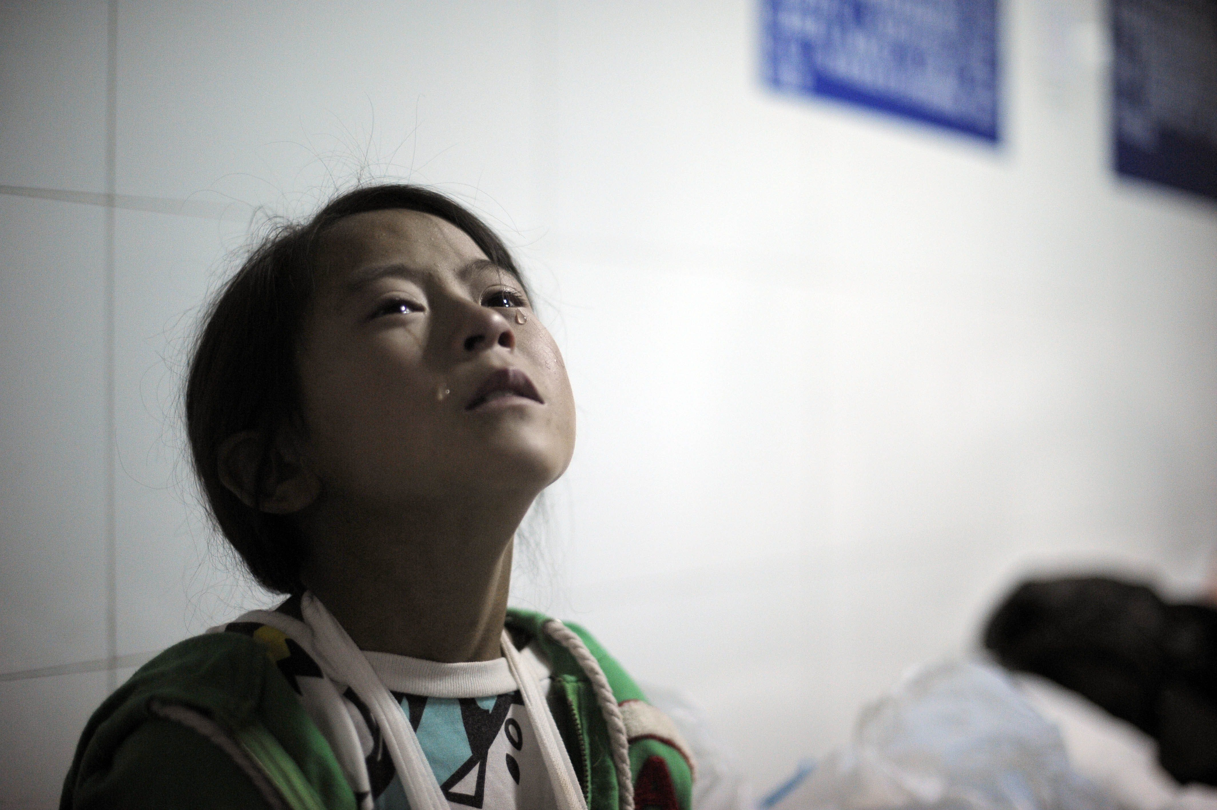 Aug. 4, 2014. An injured girl cries in the corridor of Ludian hospital after a 6.1 magnitude earthquake hit Ludian county in Zhaotong, in southwest China's Yunnan province. At least 398 people have been confirmed dead, with 80,000 houses destroyed and 124,000 seriously damaged.