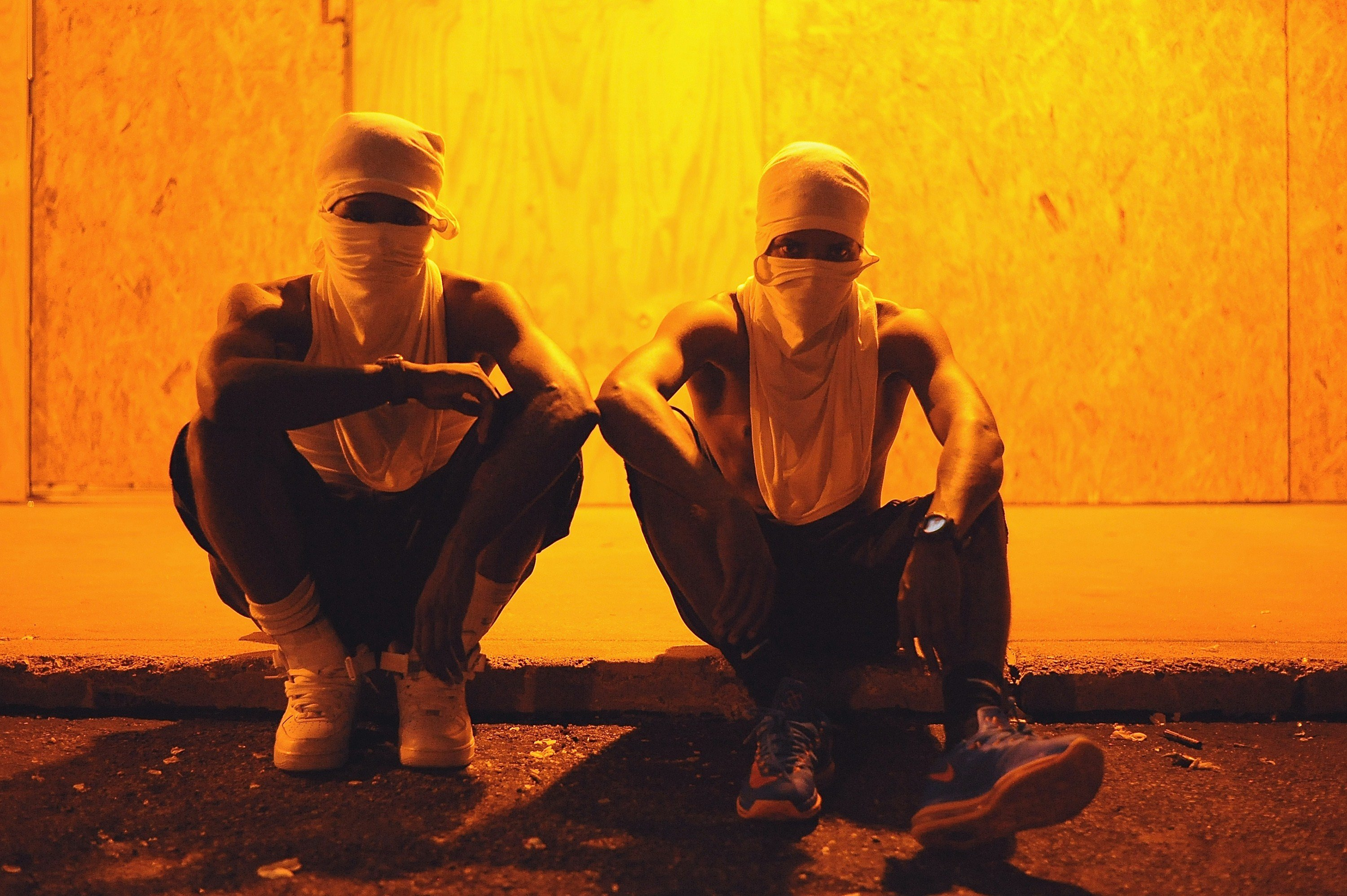 Two protesters sit with their faces covered during a peaceful protest in Ferguson, Mo. early on Aug. 20, 2014.