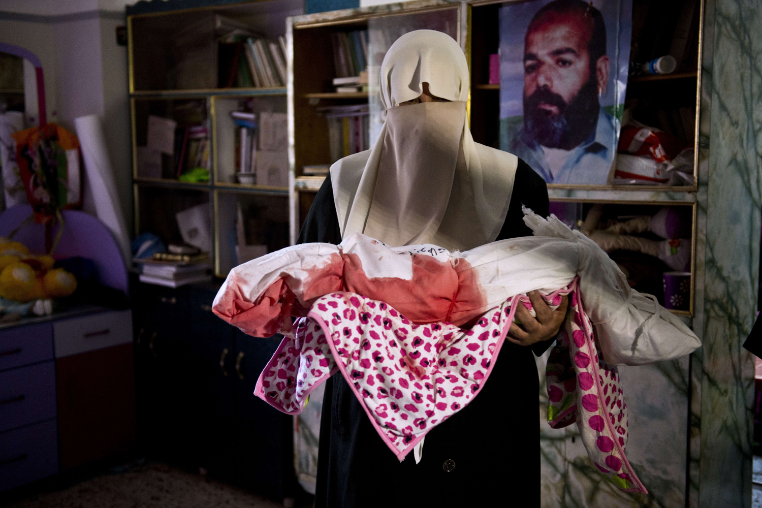 Aug. 24, 2014. A Palestinian woman holds the body of a one-and-a-half year old girl after her body was brought to the family house from the morgue before the funeral procession in Gaza City.