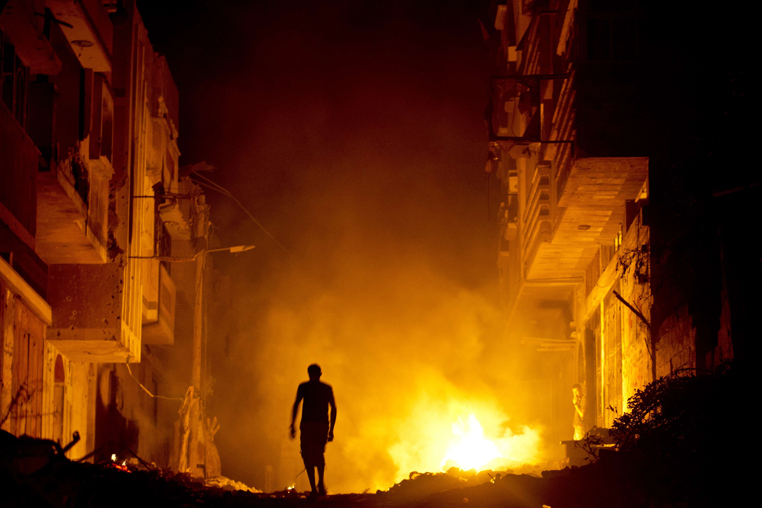 Aug. 27, 2014. A Palestinian man walks past a fire in a street set by a home owner in an effort to keep mosquitoes away from their shattered homes in Shejaiya.