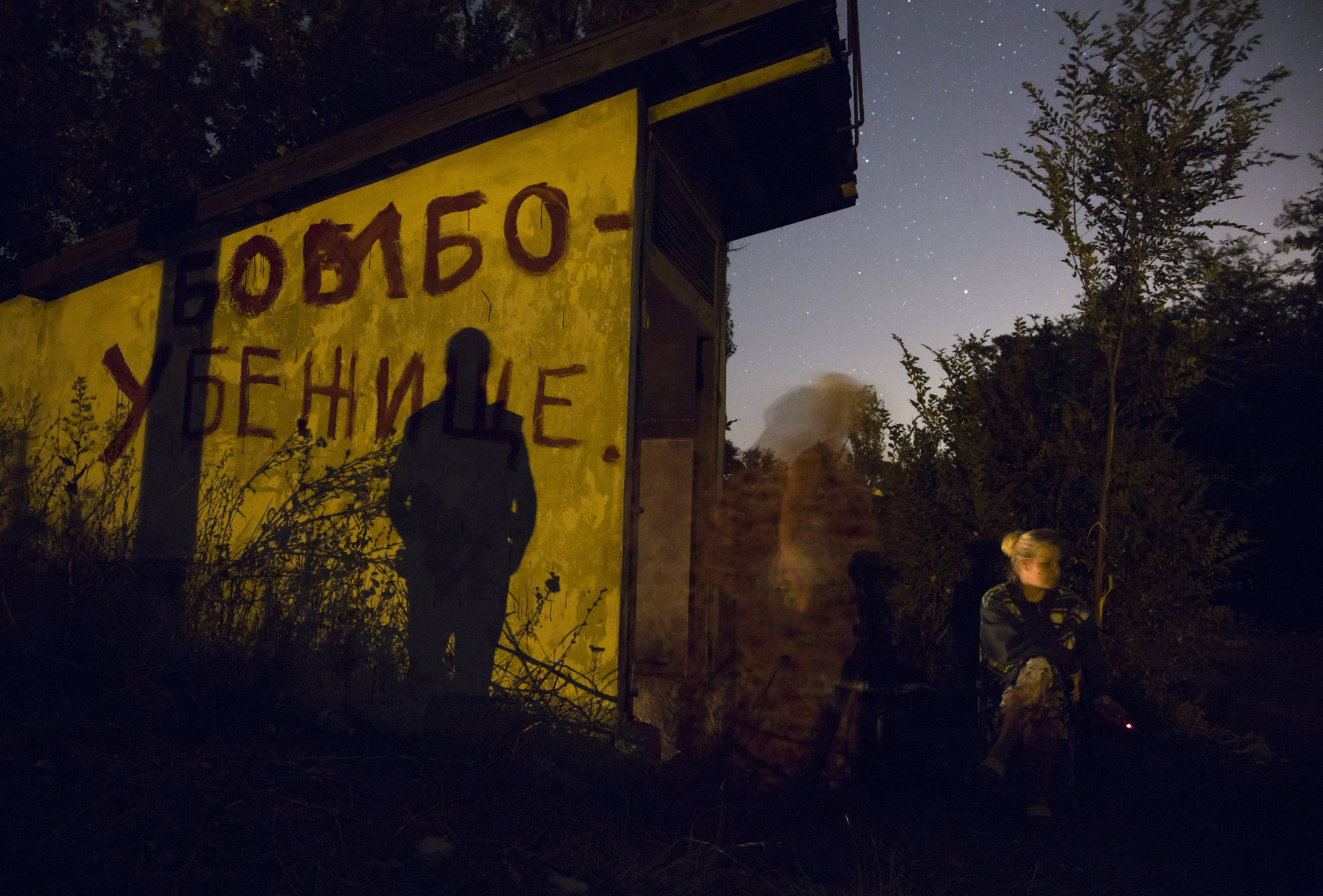 Local residents sit near an entrance to a bomb shelter as they exit to get some fresh air during a short cease fire in Petrovsky district in the city of Donetsk, eastern Ukraine, Aug. 5, 2014.